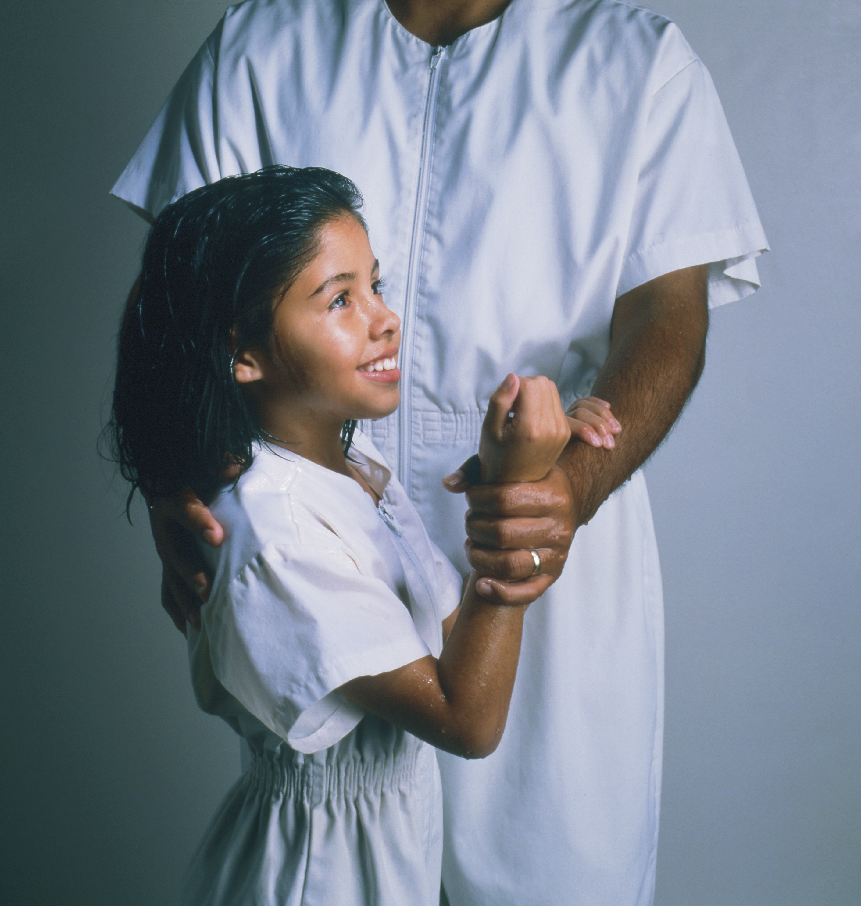 An eight-year-old girl and a priesthood holder dressed in white baptismal clothing, in position for baptism.