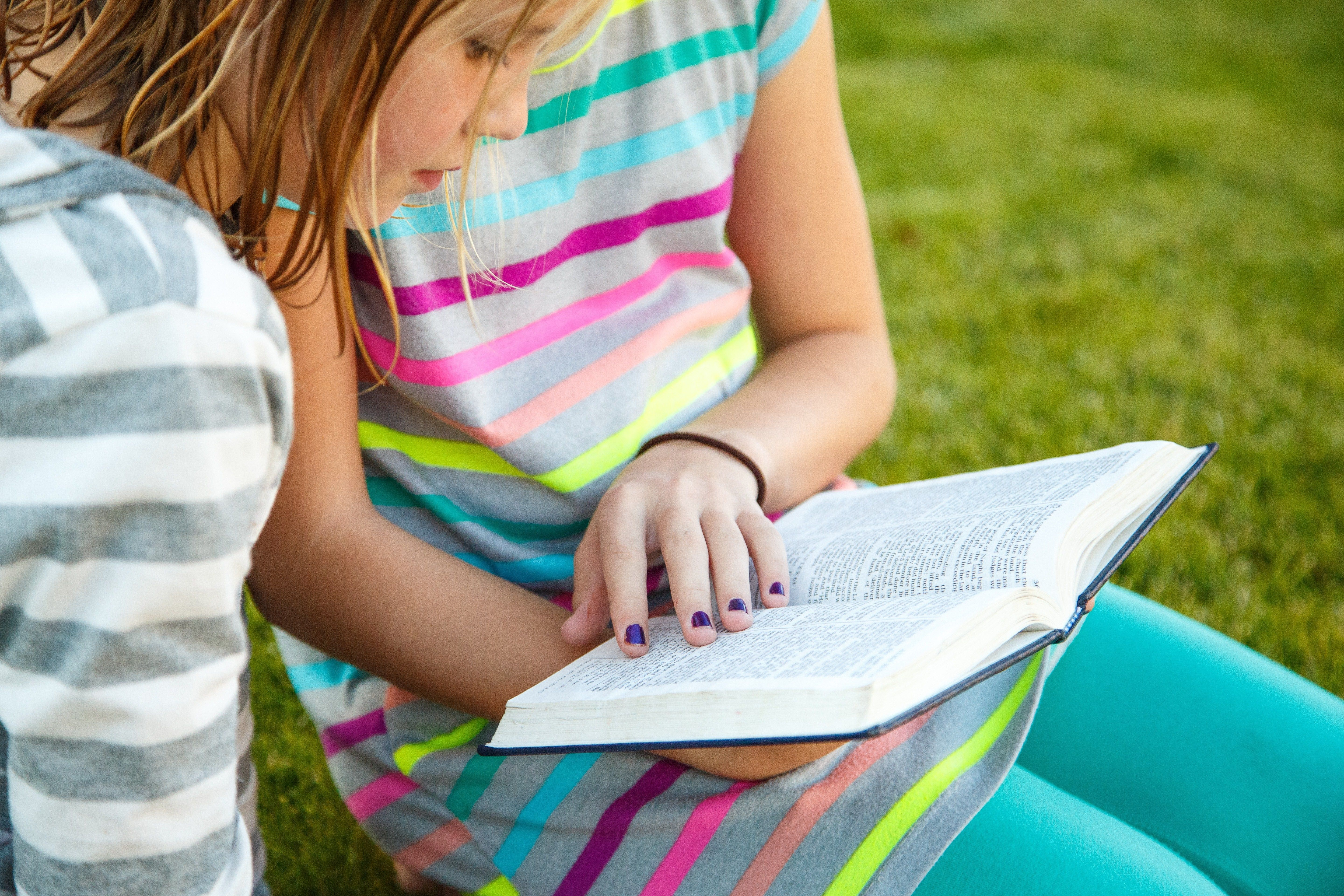 Two young girls sit on the grass and read the Book of Mormon together.