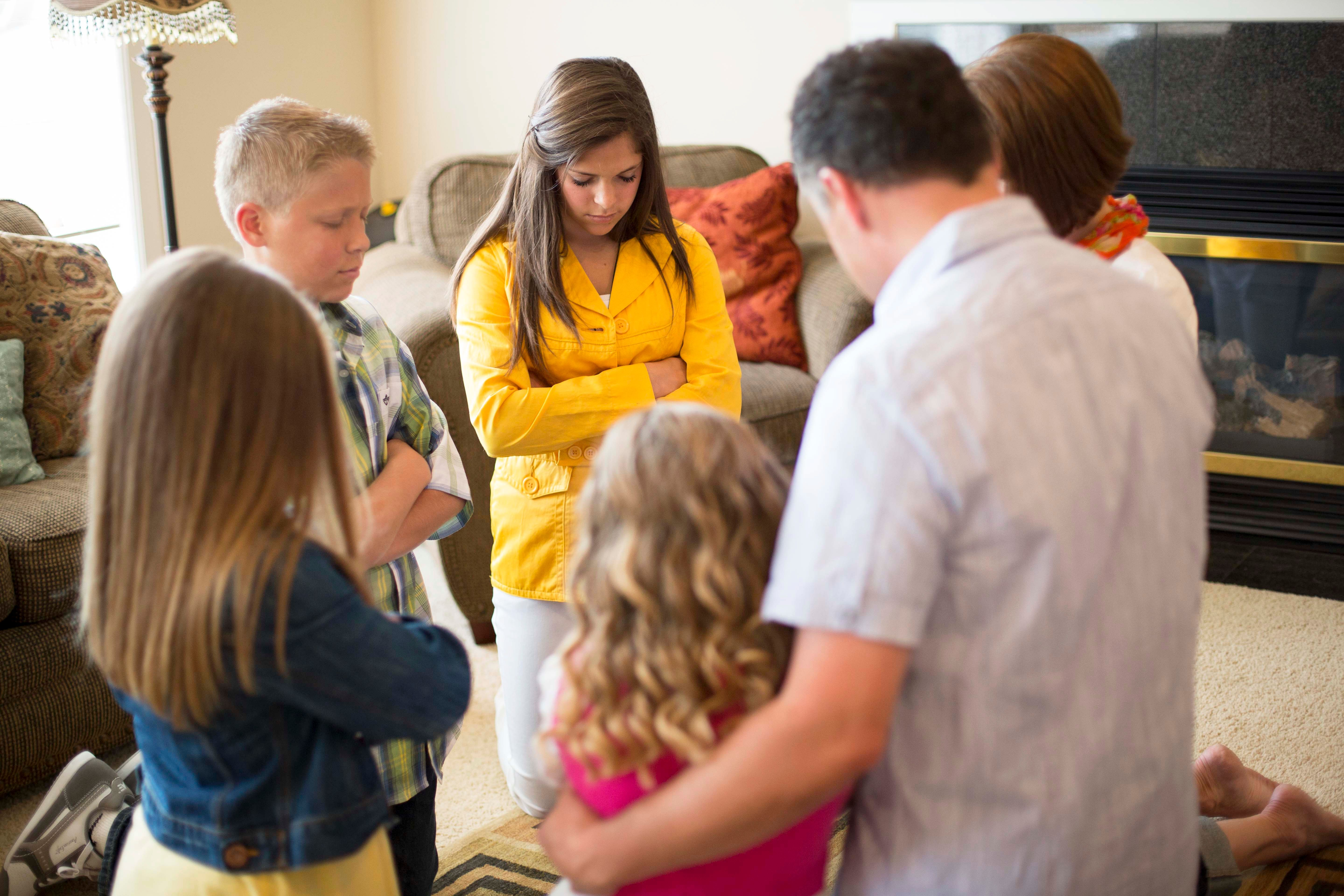 A family kneeling in the living room to pray together.