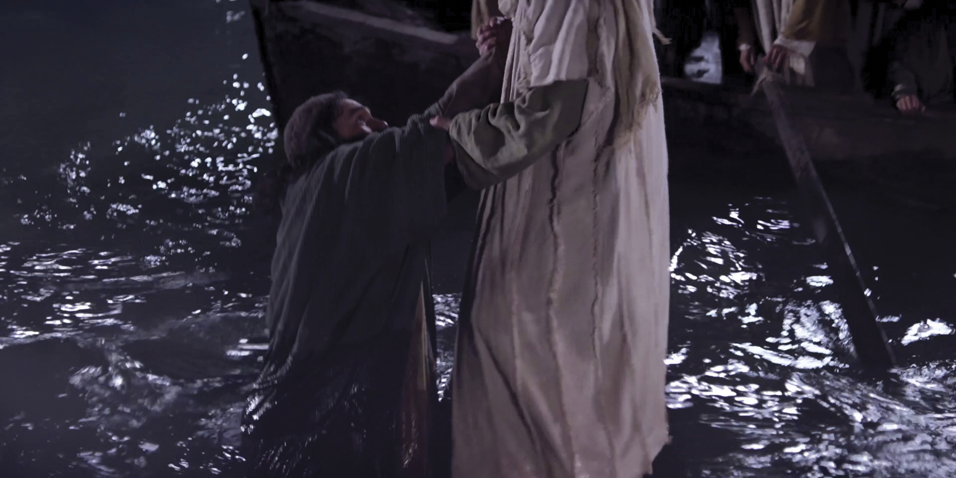 Christ reaches down to pull Peter out of the water after Peter doubts and begins to sink.