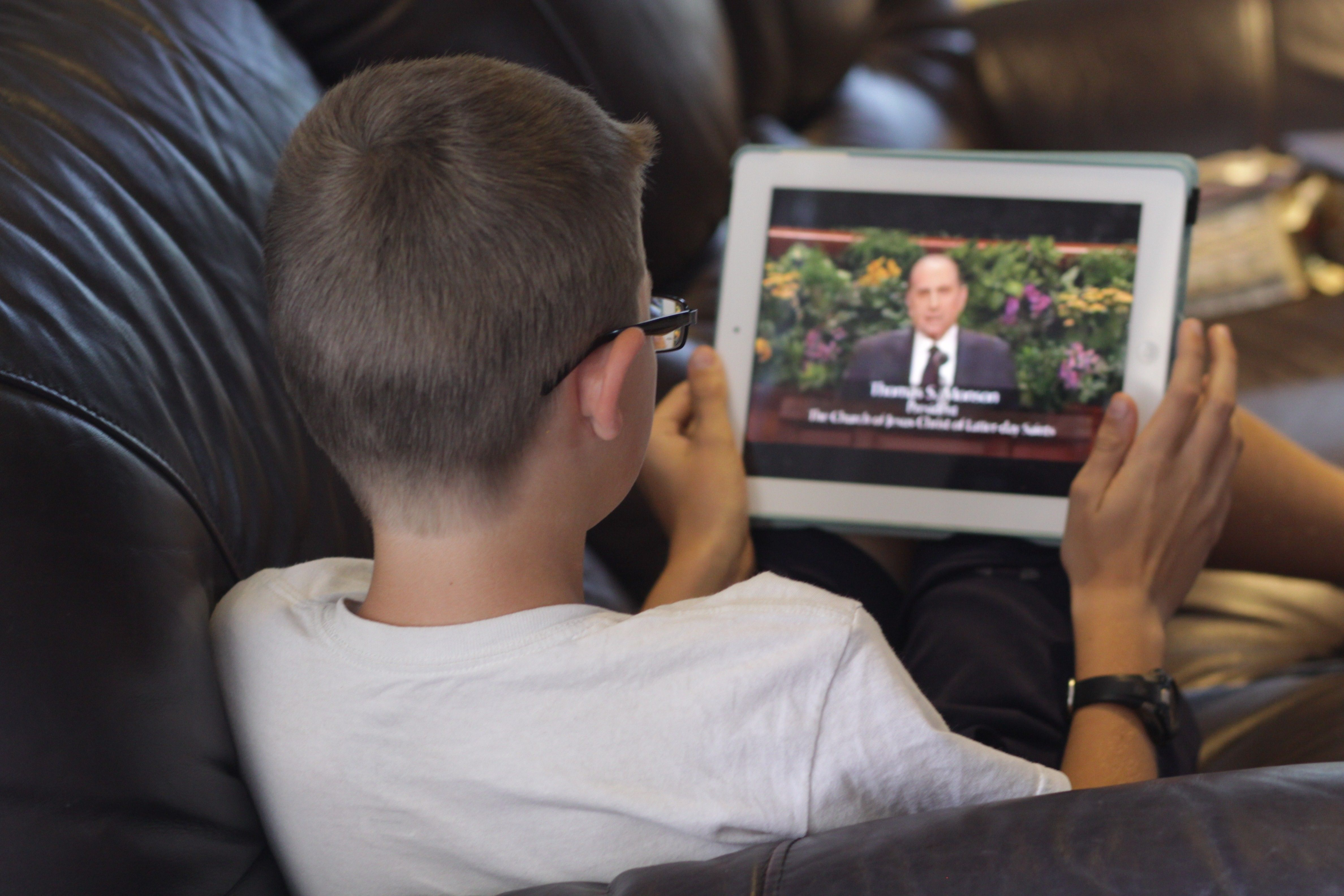 A boy sitting at home watching general conference on his tablet.