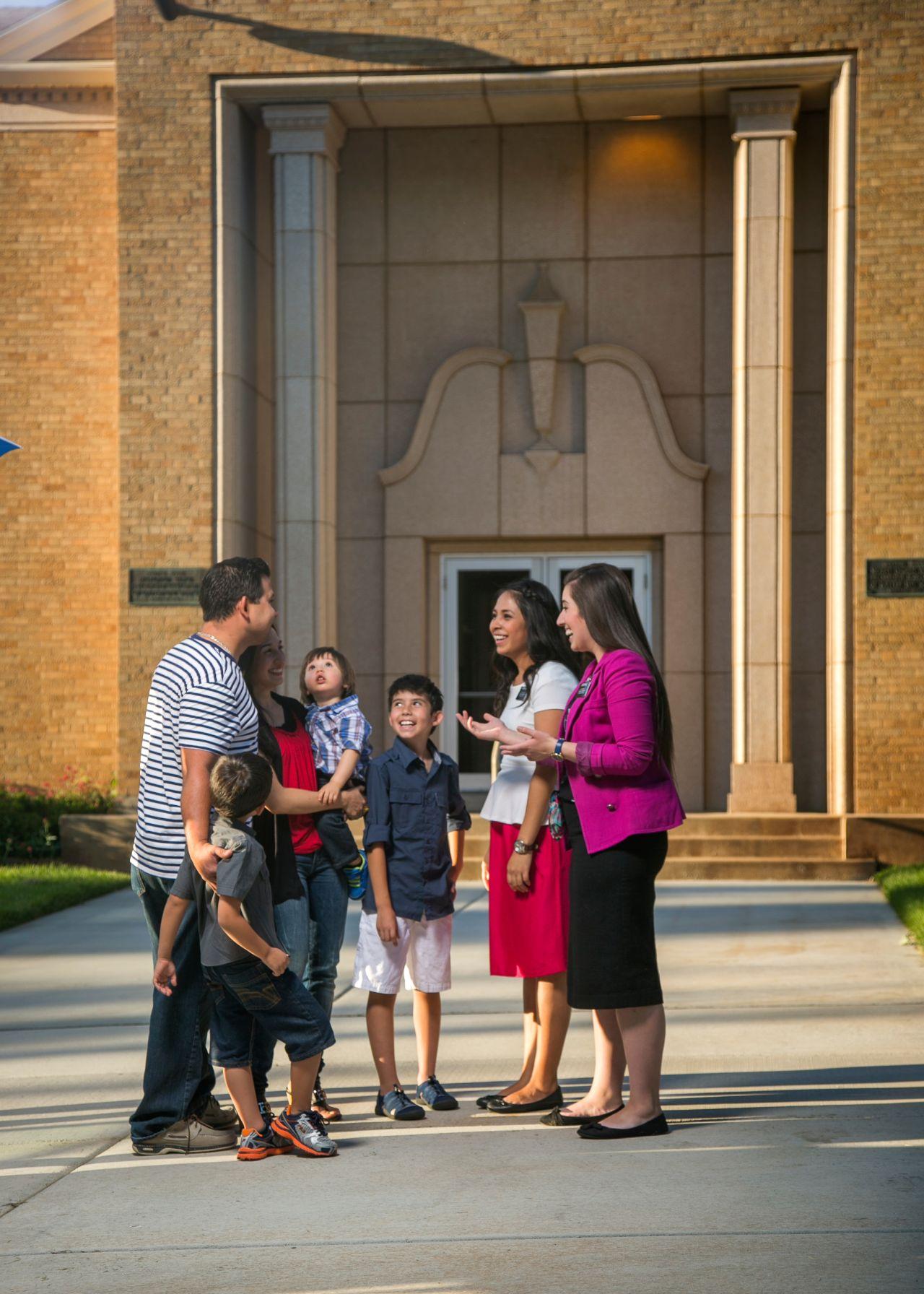 una familia visita una capilla, guida por misioneras