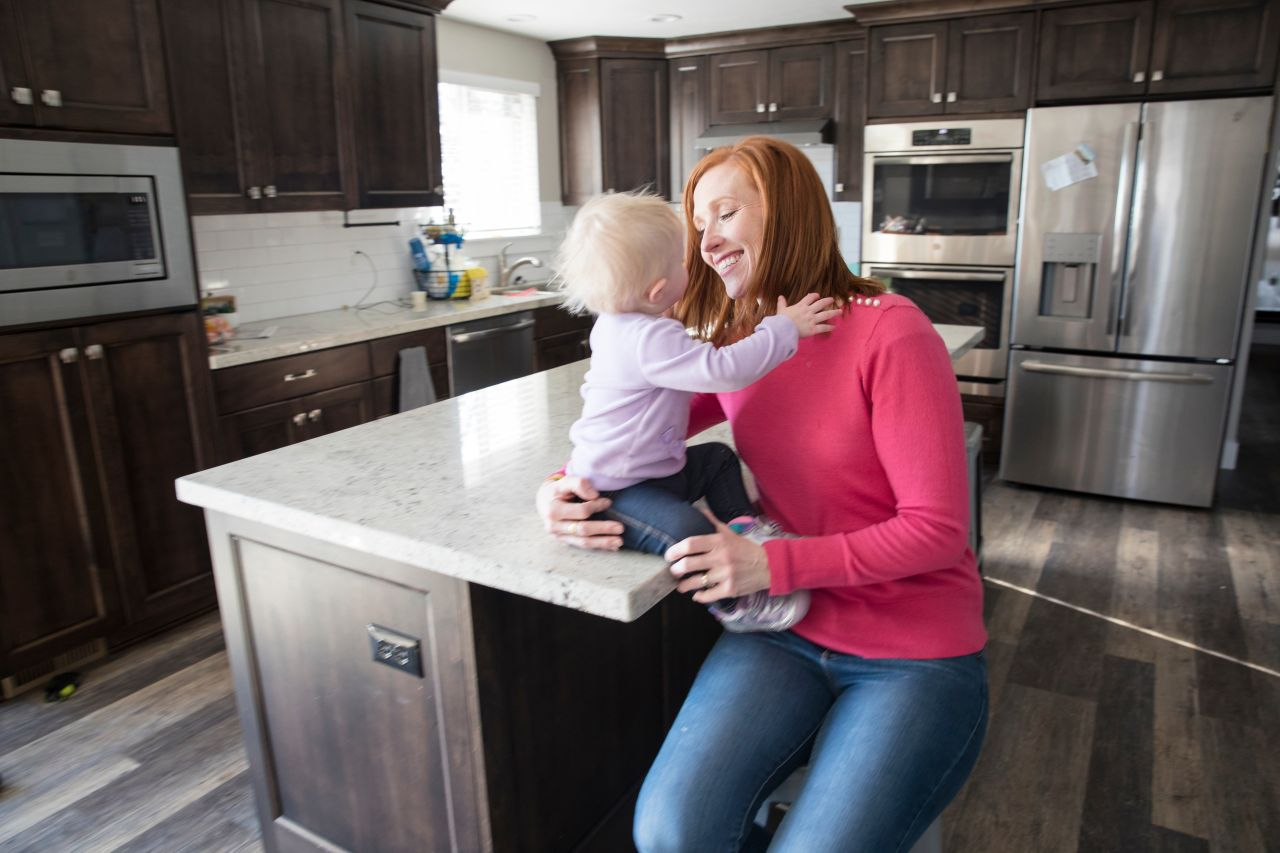 A mother sits with her young child in their kitchen