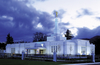 The Medford Oregon Temple exterior and grounds are lit up in the late evening, with a stormy sky in the distance.