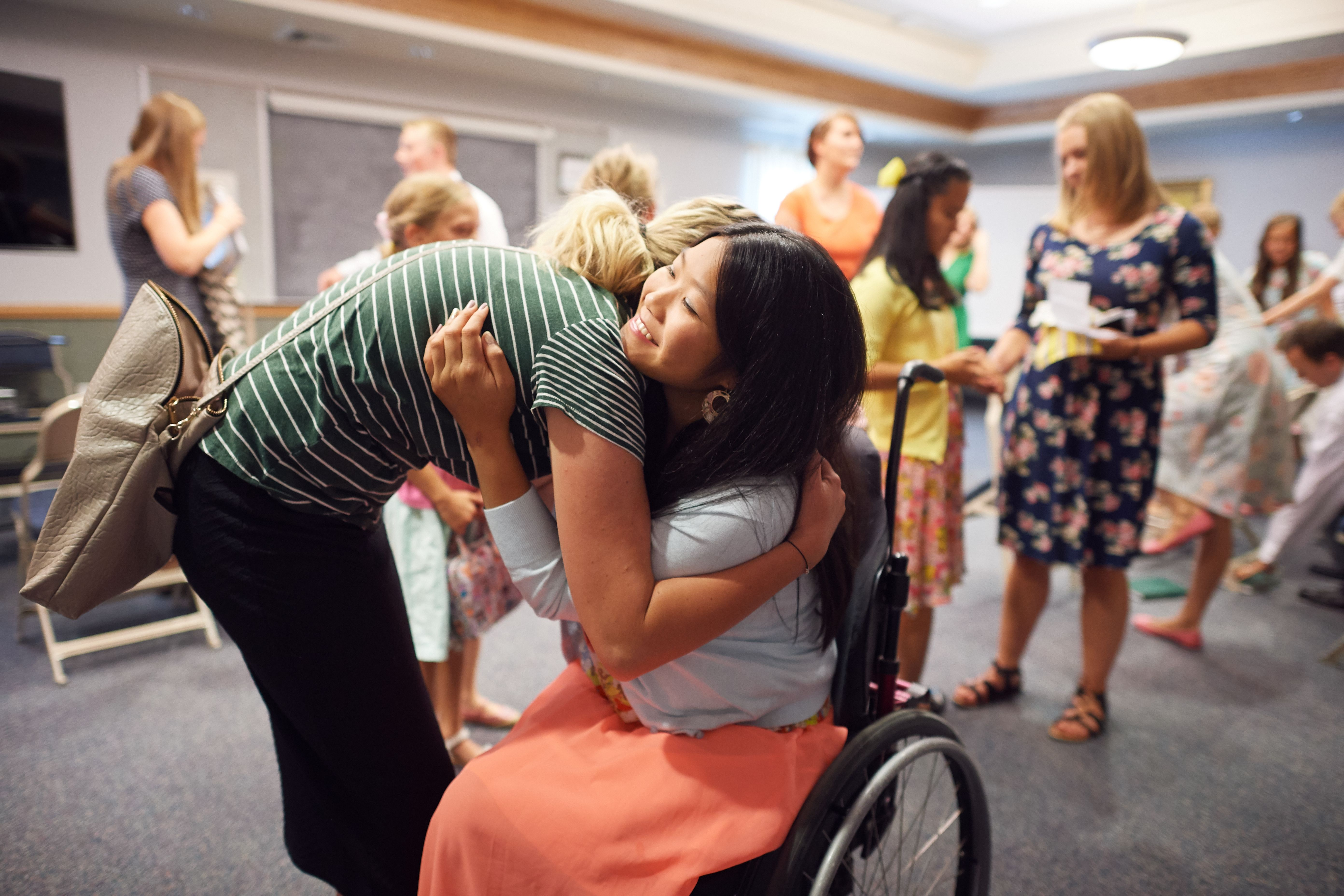 A young woman in a green striped shirt and black skirt leans down to hug her friend who is sitting in a wheelchair.