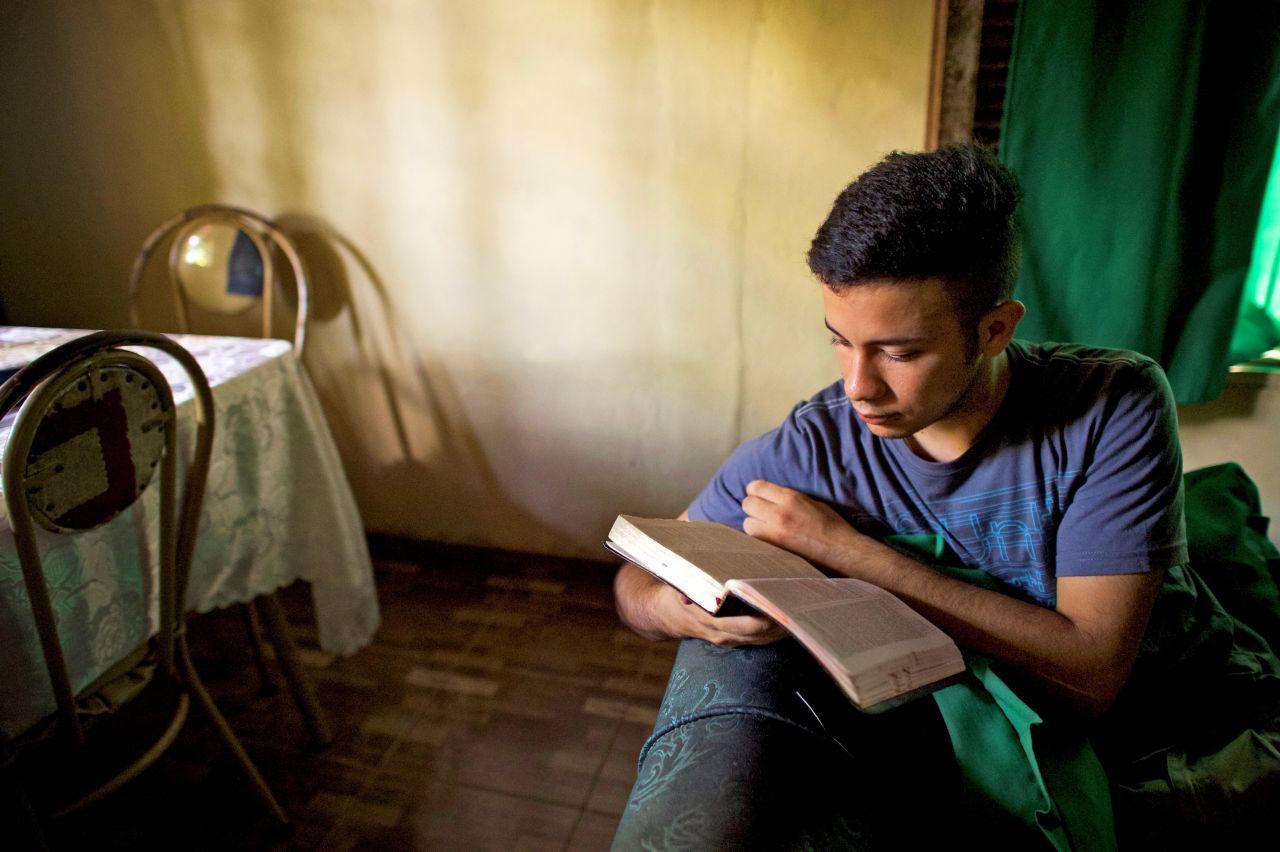 Un joven lee la biblia