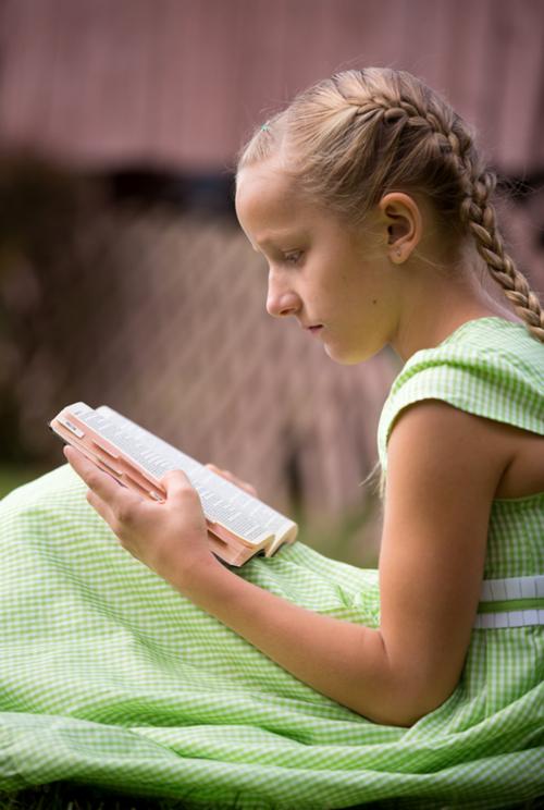 Ein Mädchen liest im Buch Mormon