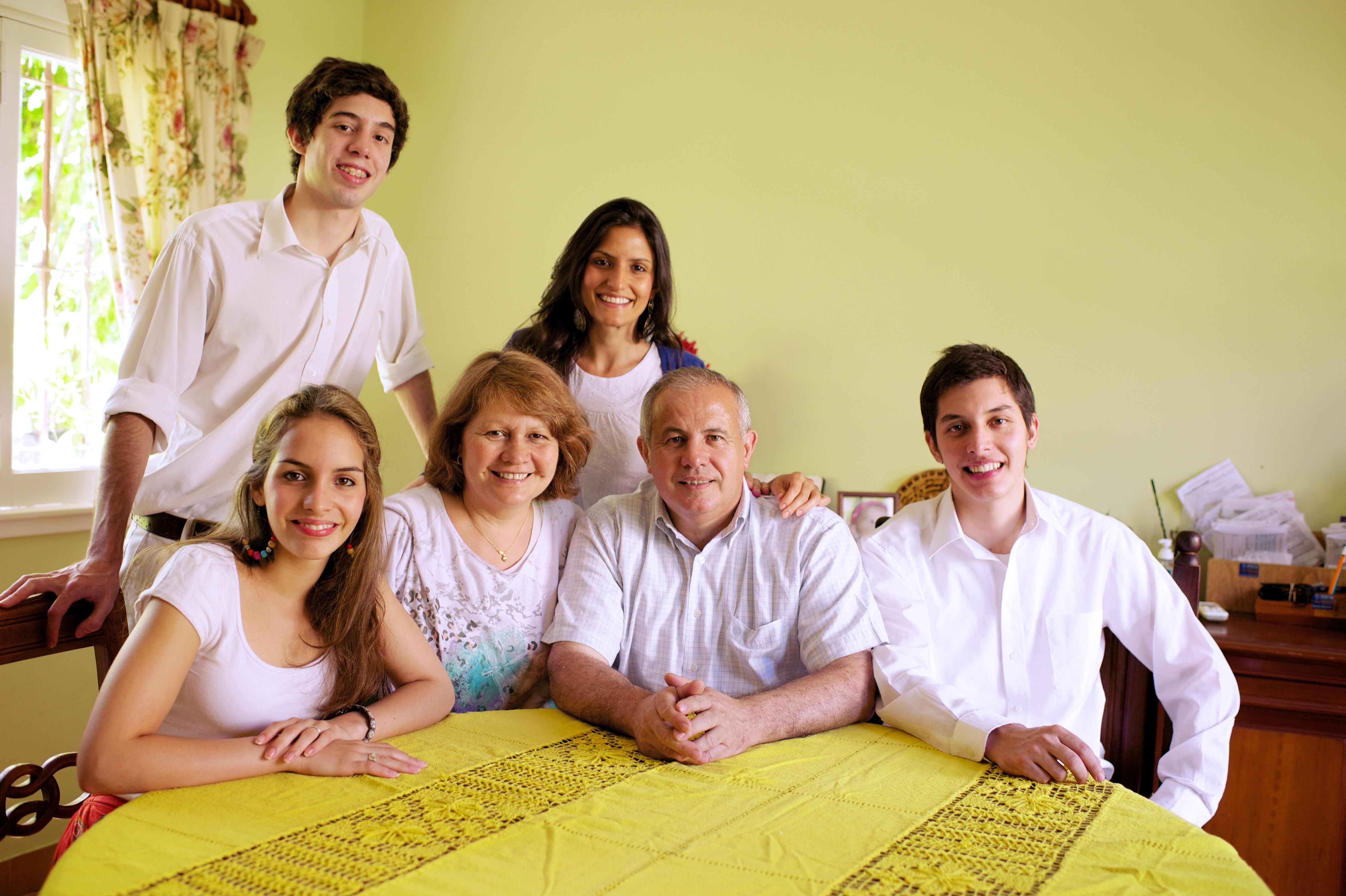 An informal portrait of a family in Argentina sitting at their dinner table.
