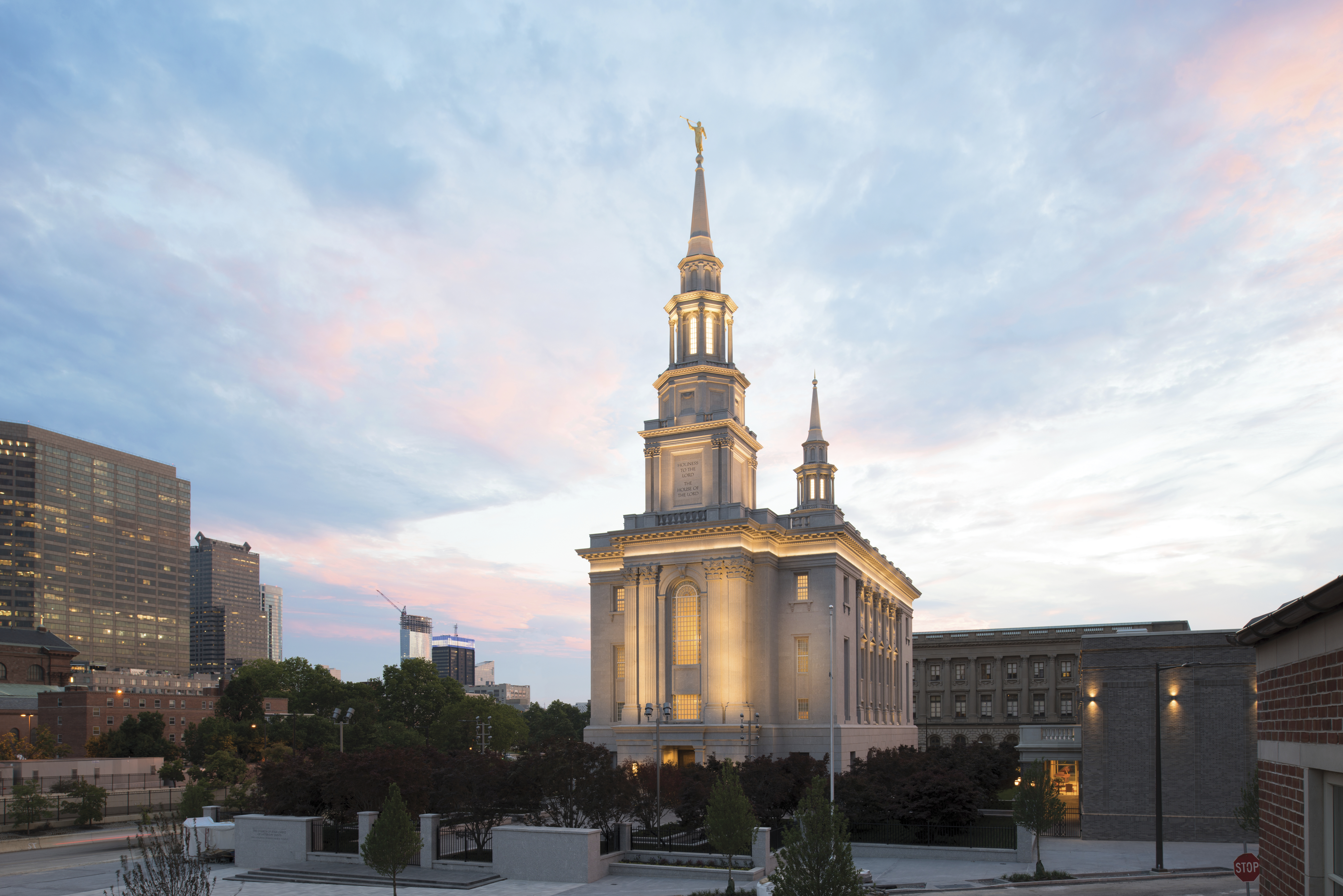 An exterior view of the Philadelphia Pennsylvania Temple with its lights on during a sunset.
