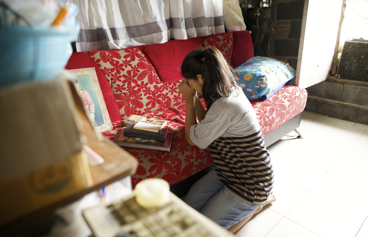 A young woman kneels in prayer in her living room asking God to please help her