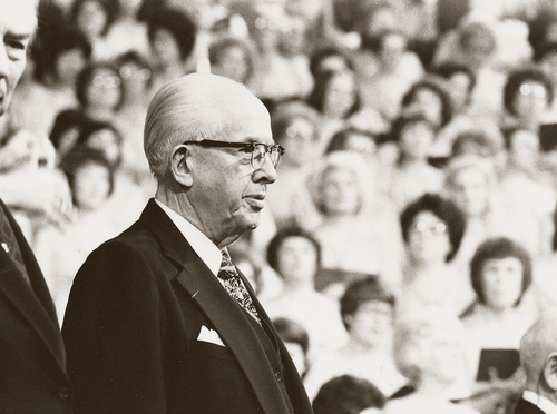 President Benson in a suit, a white shirt, and glasses, standing and speaking to the audience at general conference.