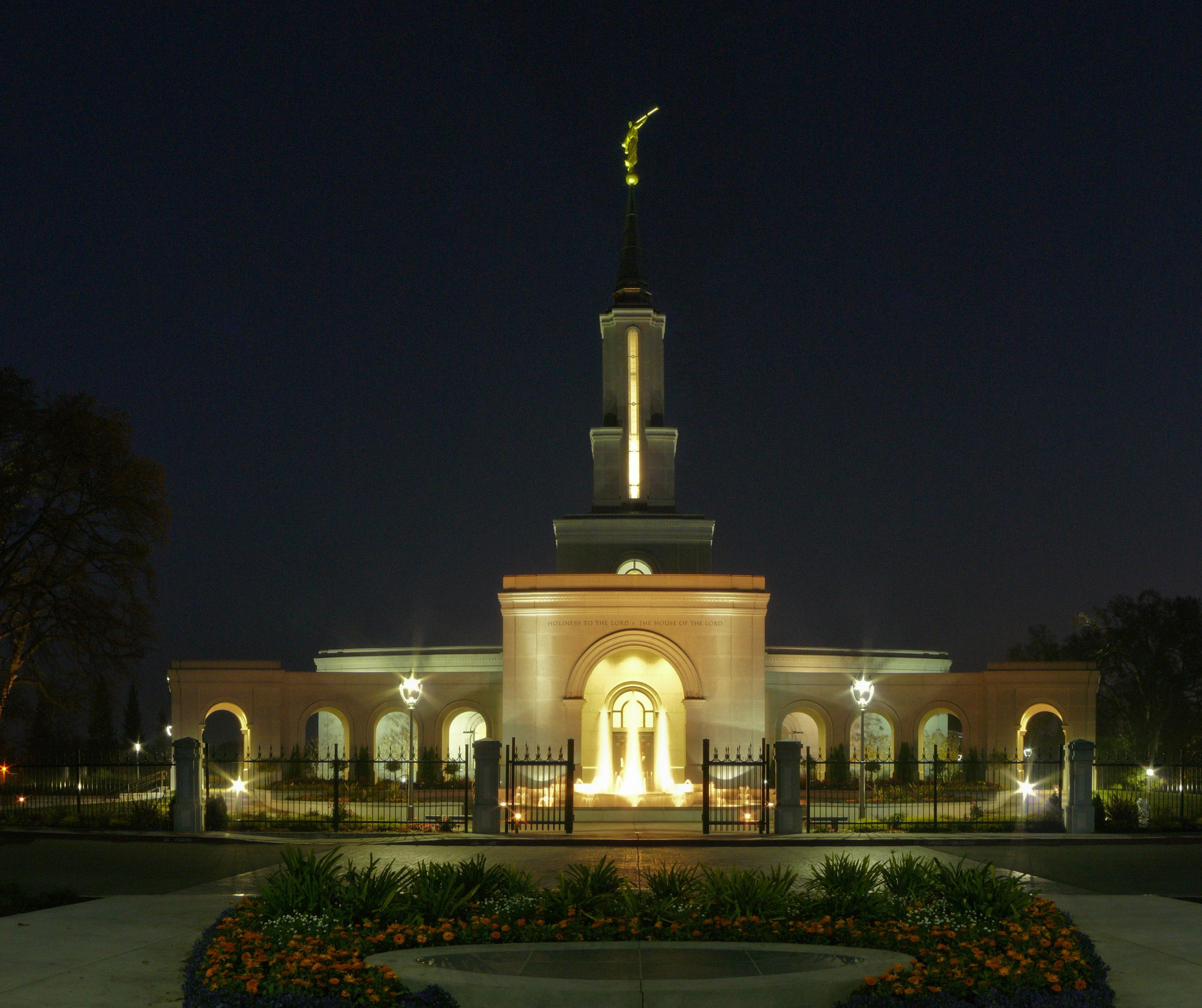 The Sacramento California Temple in the evening, including the fountains and entrance.
