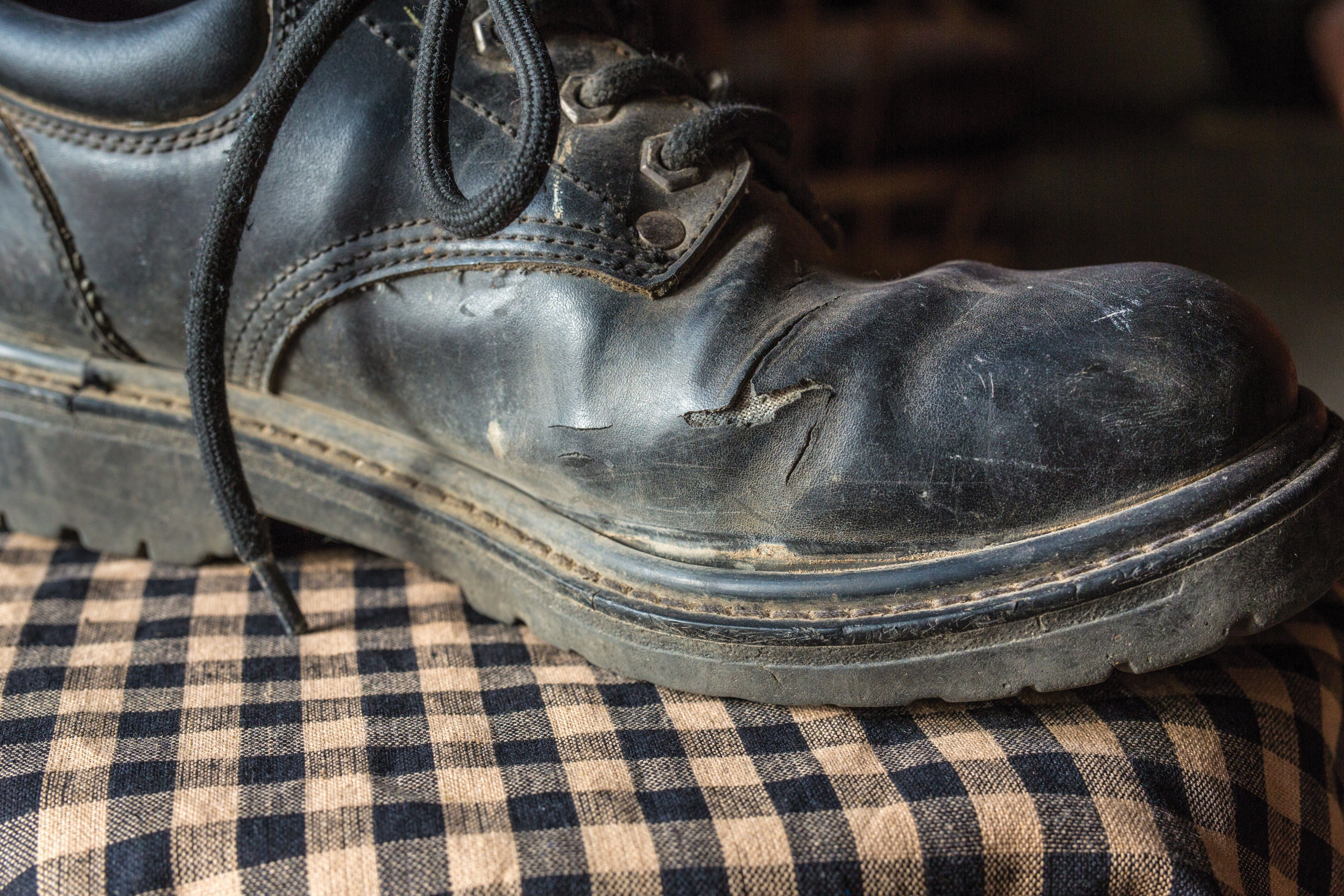 An old black shoe that has begun to wear out.