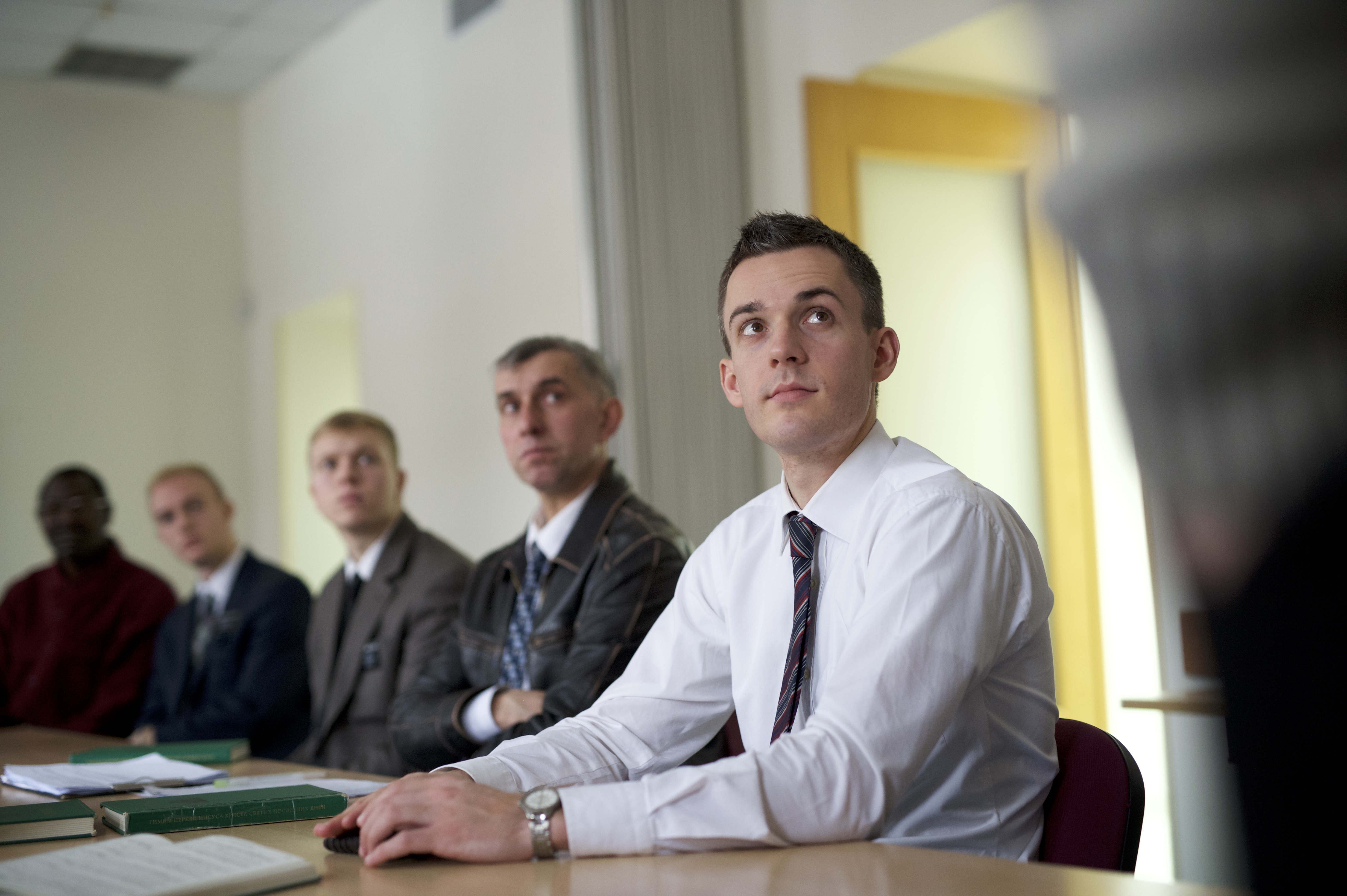A group of men attending priesthood quorum meetings.
