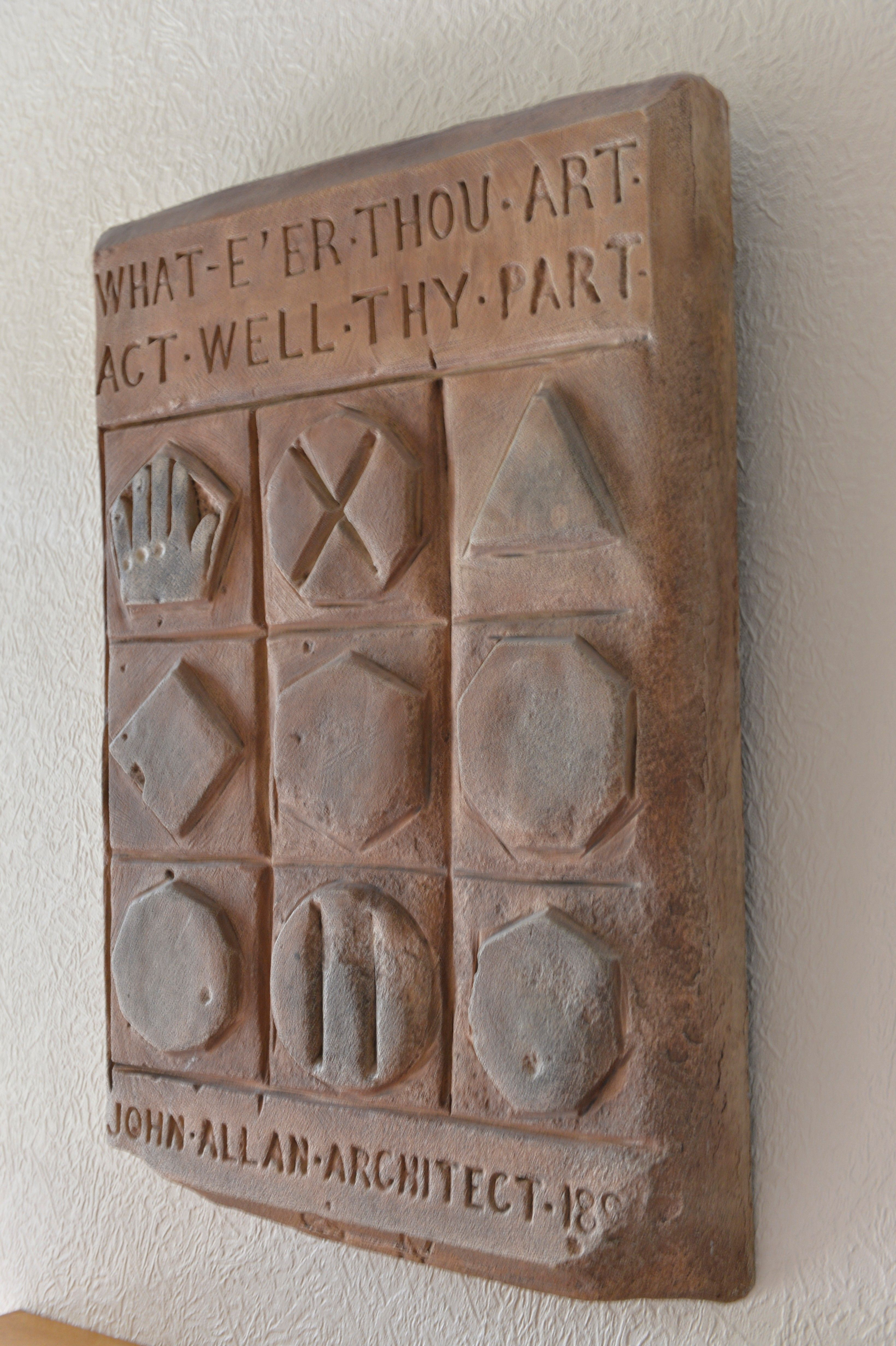"""A replica of the plaque with the statement """"What E'er Thou Art, Act Well Thy Part."""""""