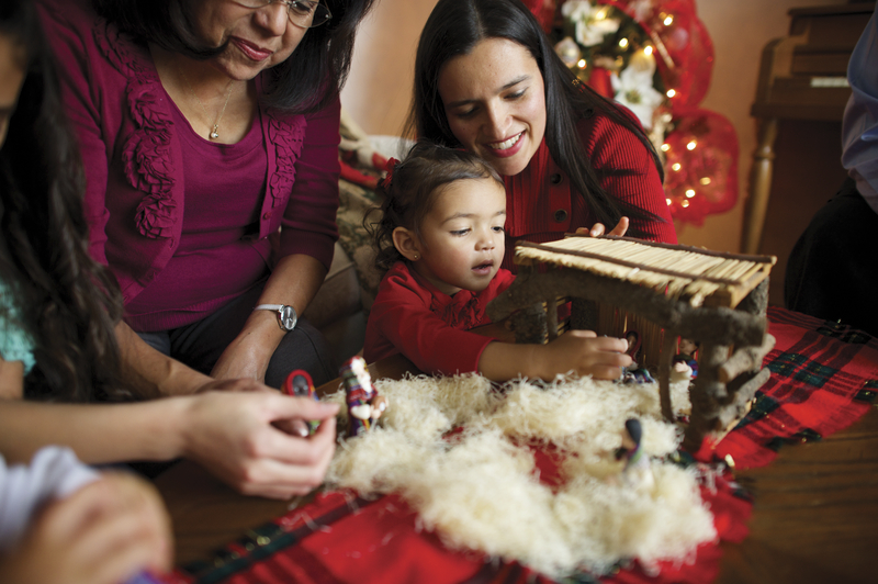 A young girl and her family standing around a table and setting up a small Nativity.