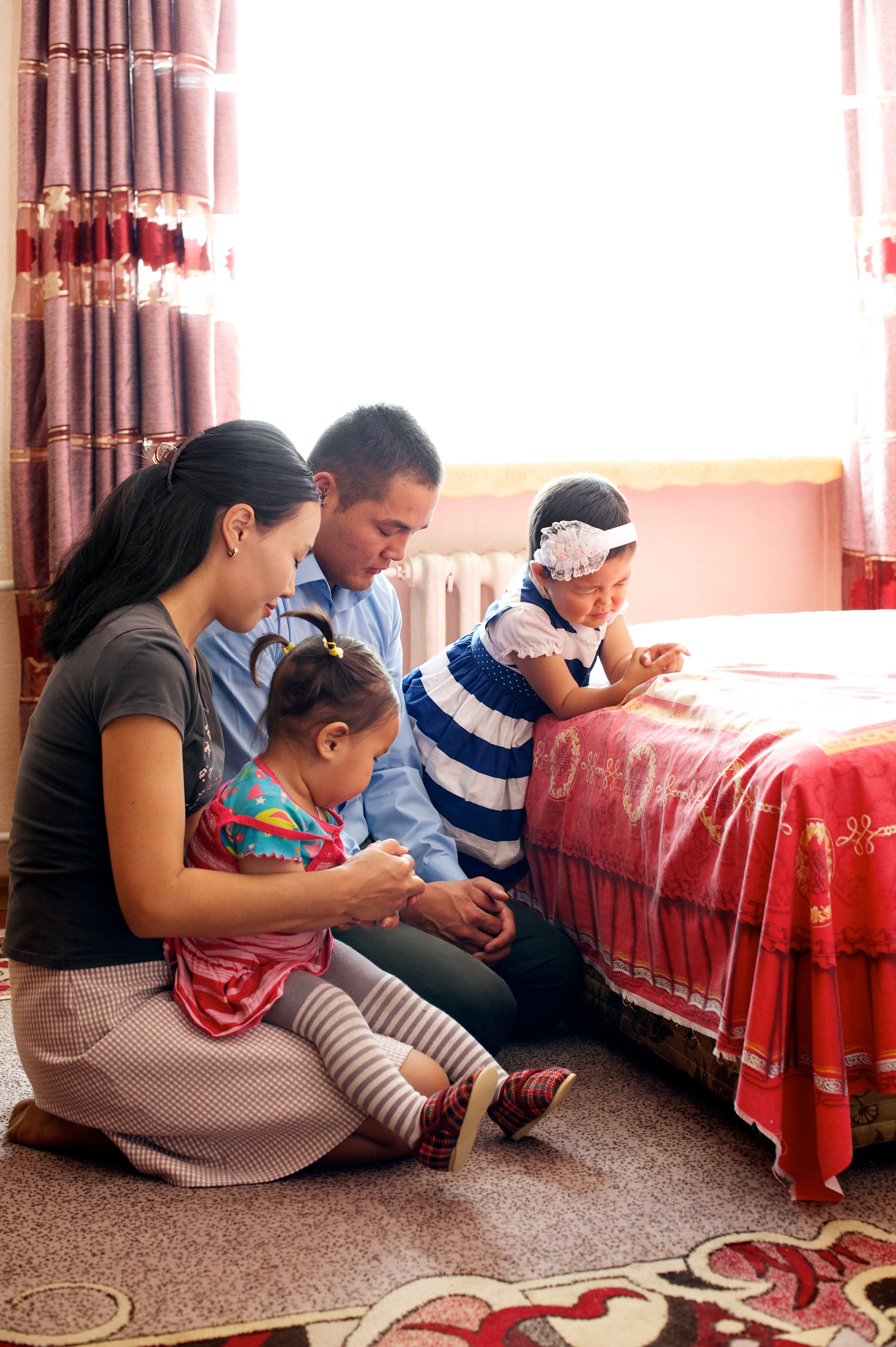 A family kneeling by the bed to pray together.