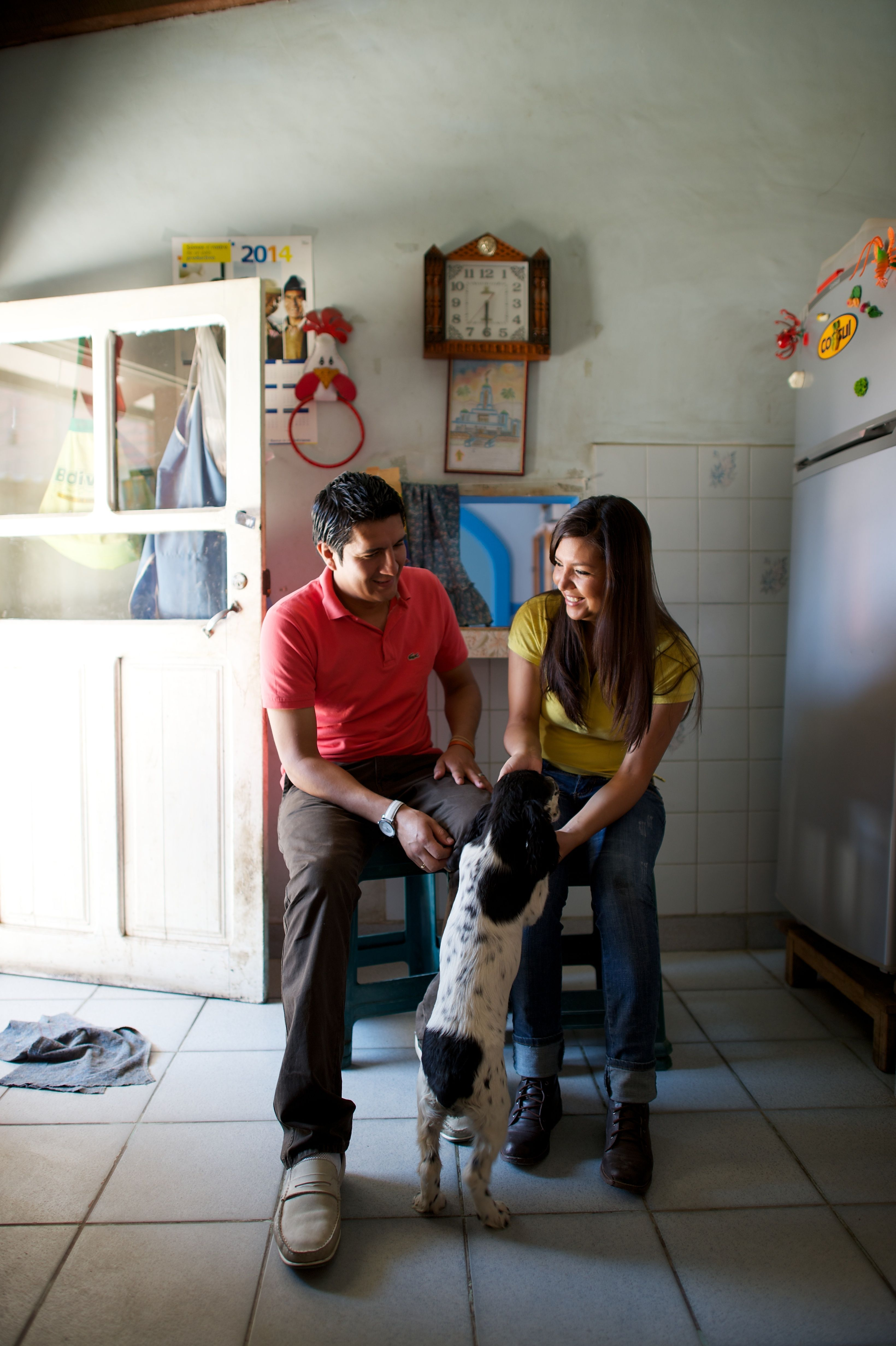 A young couple sitting on stools inside a kitchen and playing with a dog.