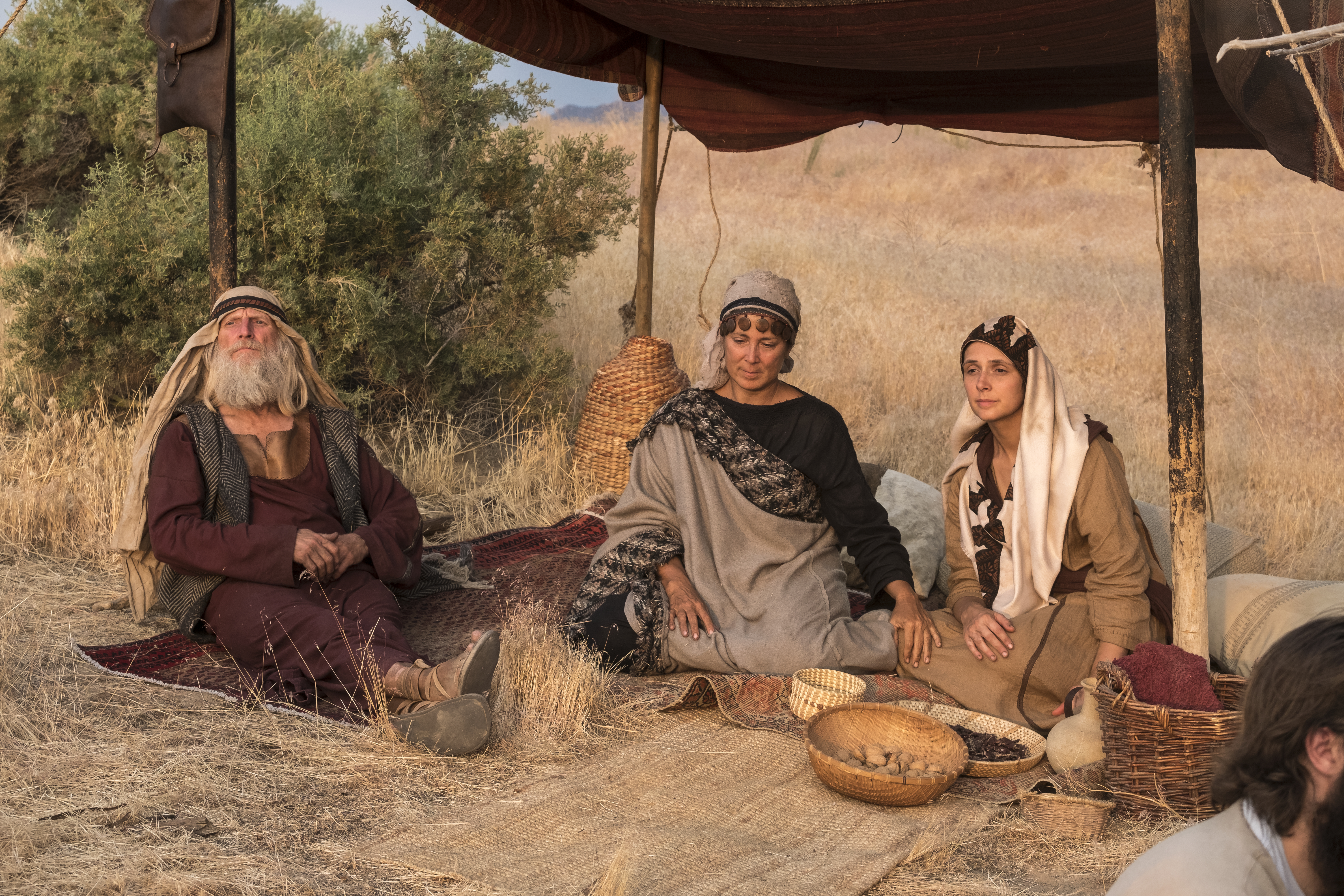Ishmael, his wife, and his daughter sit in a tent in the wilderness.