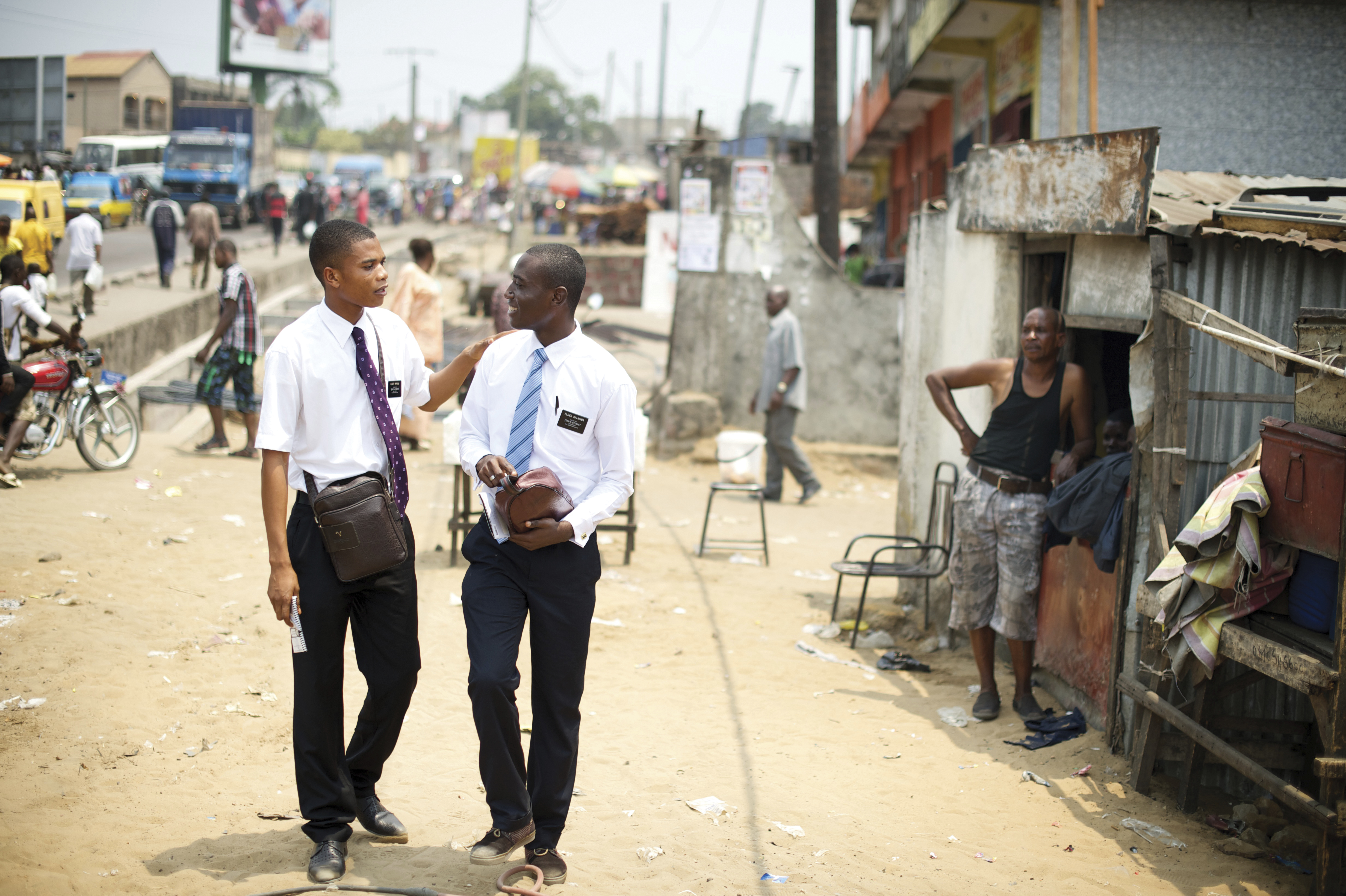 Two missionaries from Africa talking and walking down a street.