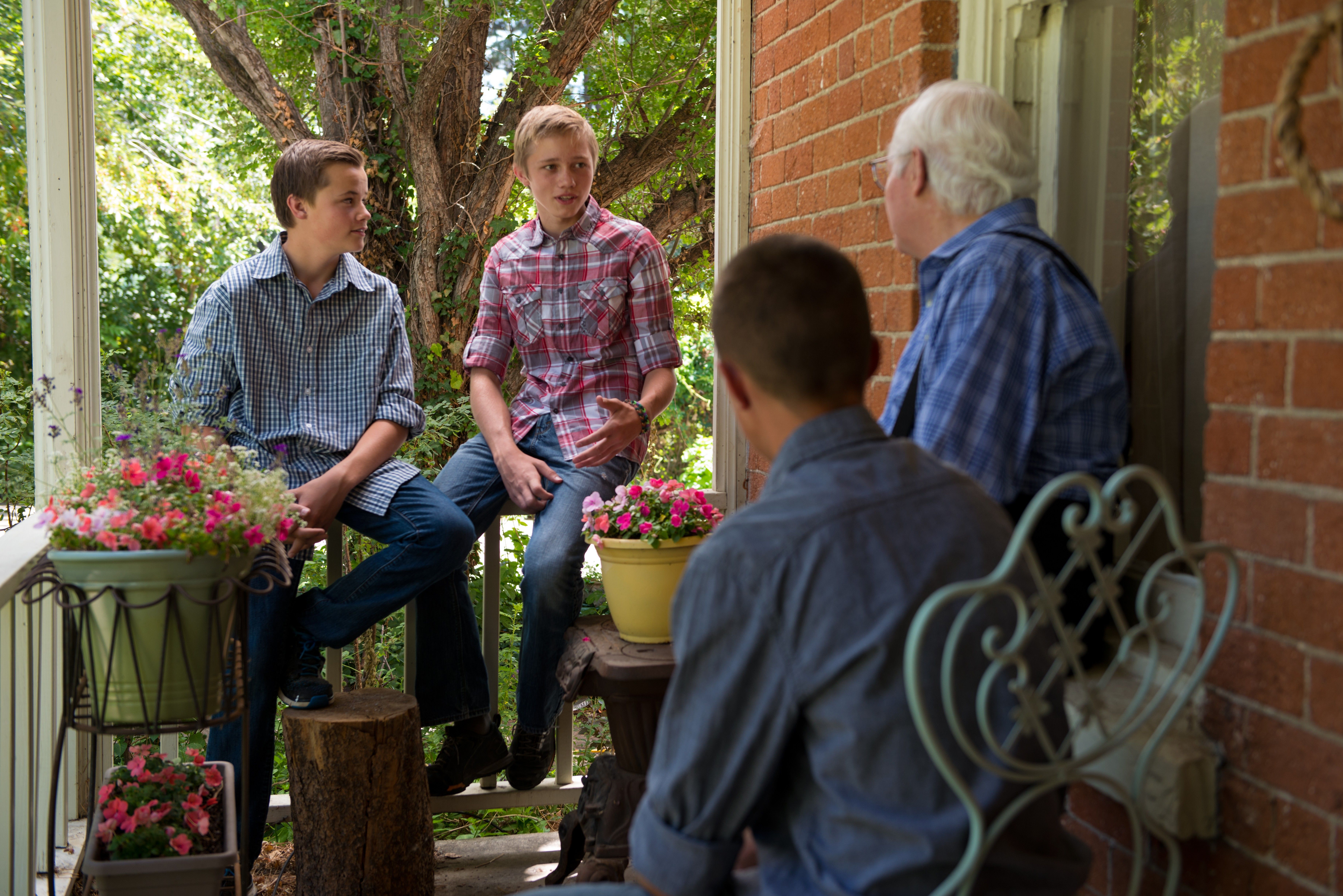 Three young men sit on a porch with an elderly man and talk with him.