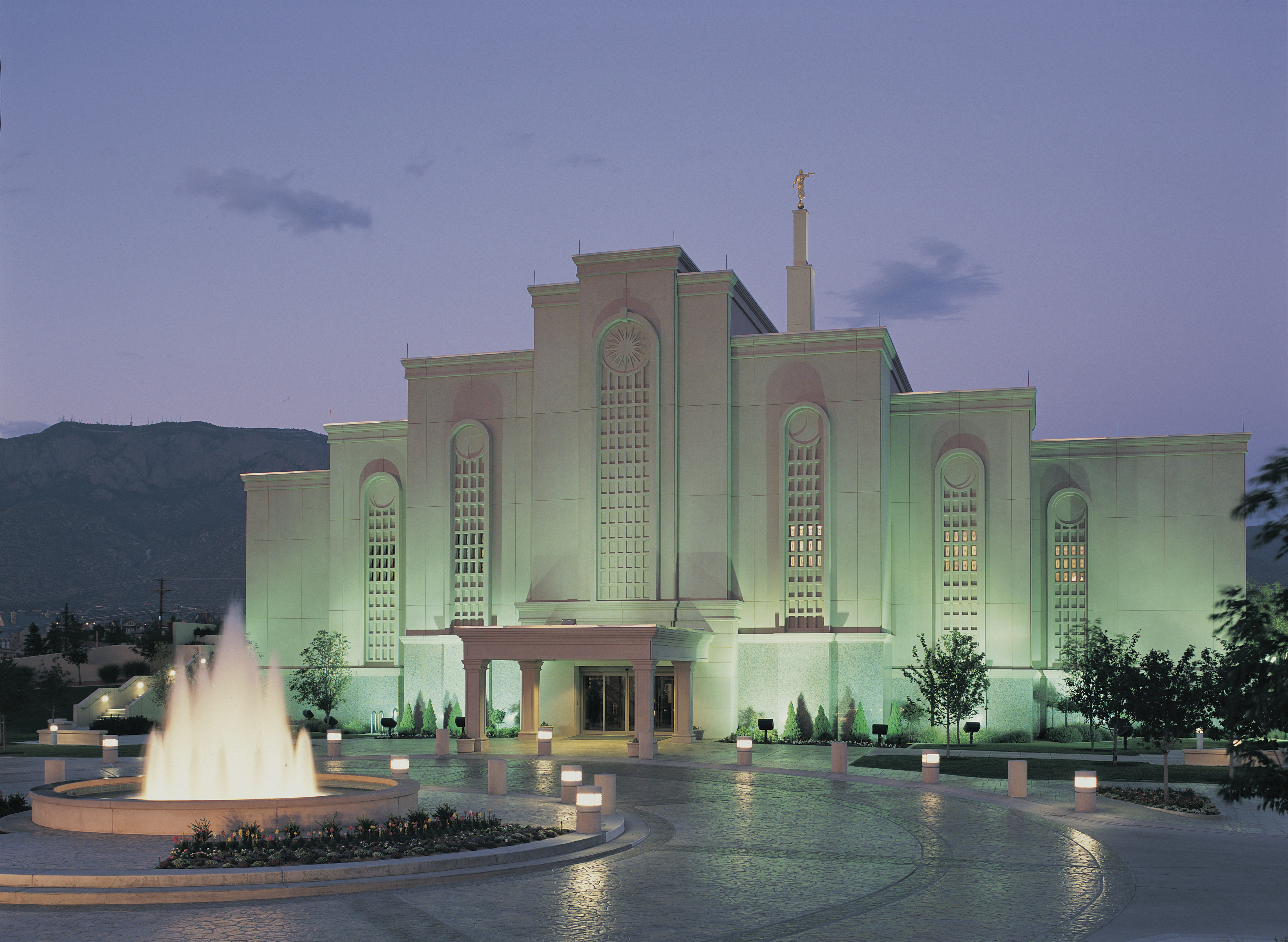 The exterior of the Albuquerque New Mexico Temple and grounds are lit up at night.