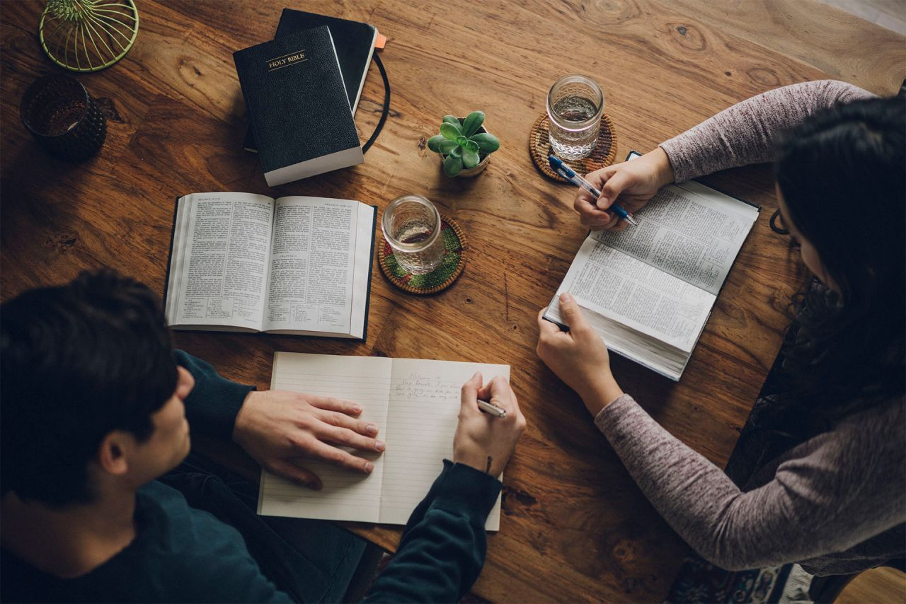 A couple sit together at their kitchen table studying God's message for them