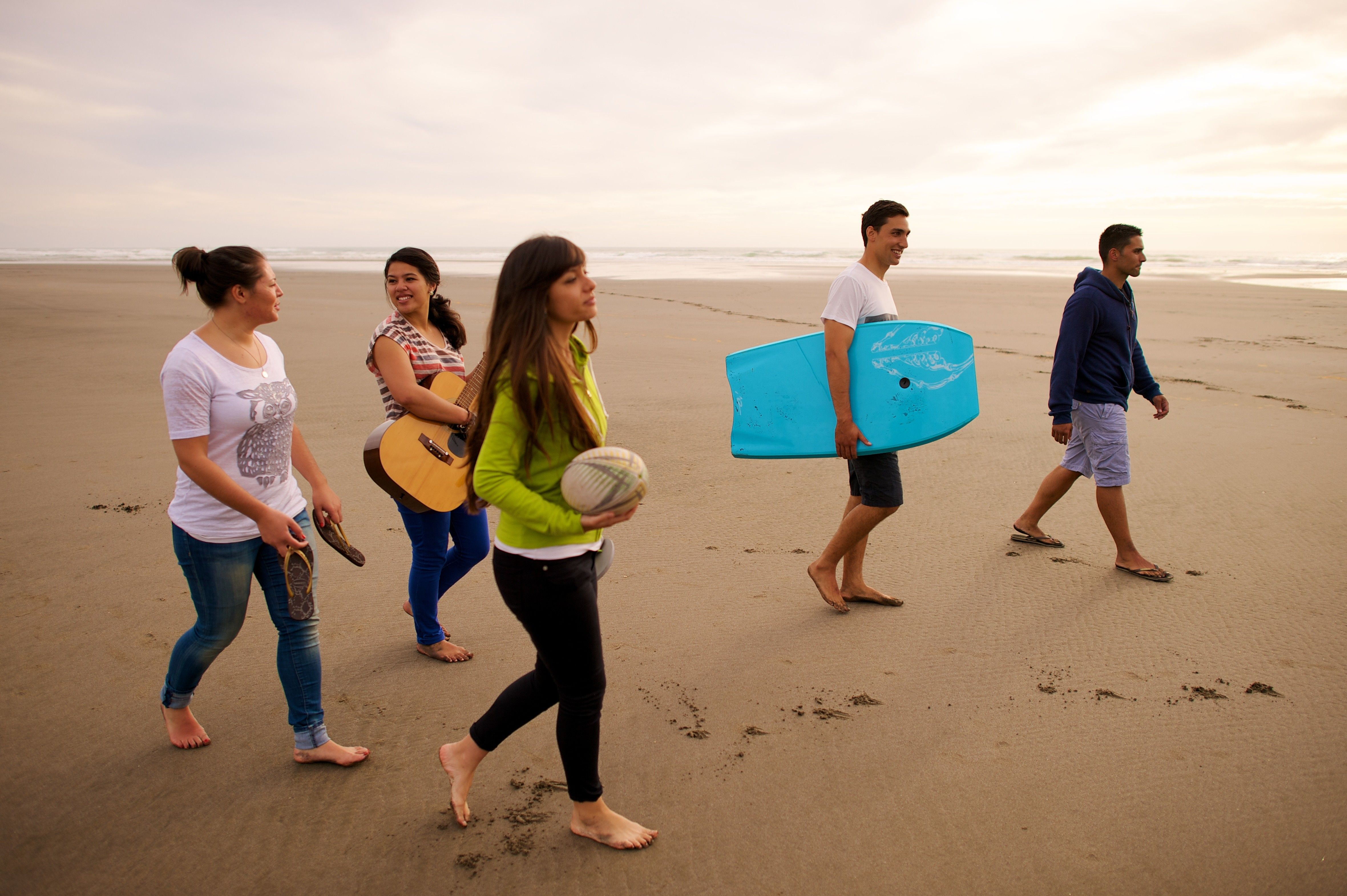 A group of youth go out on the beach together to bodyboard, play ball, and play guitar.