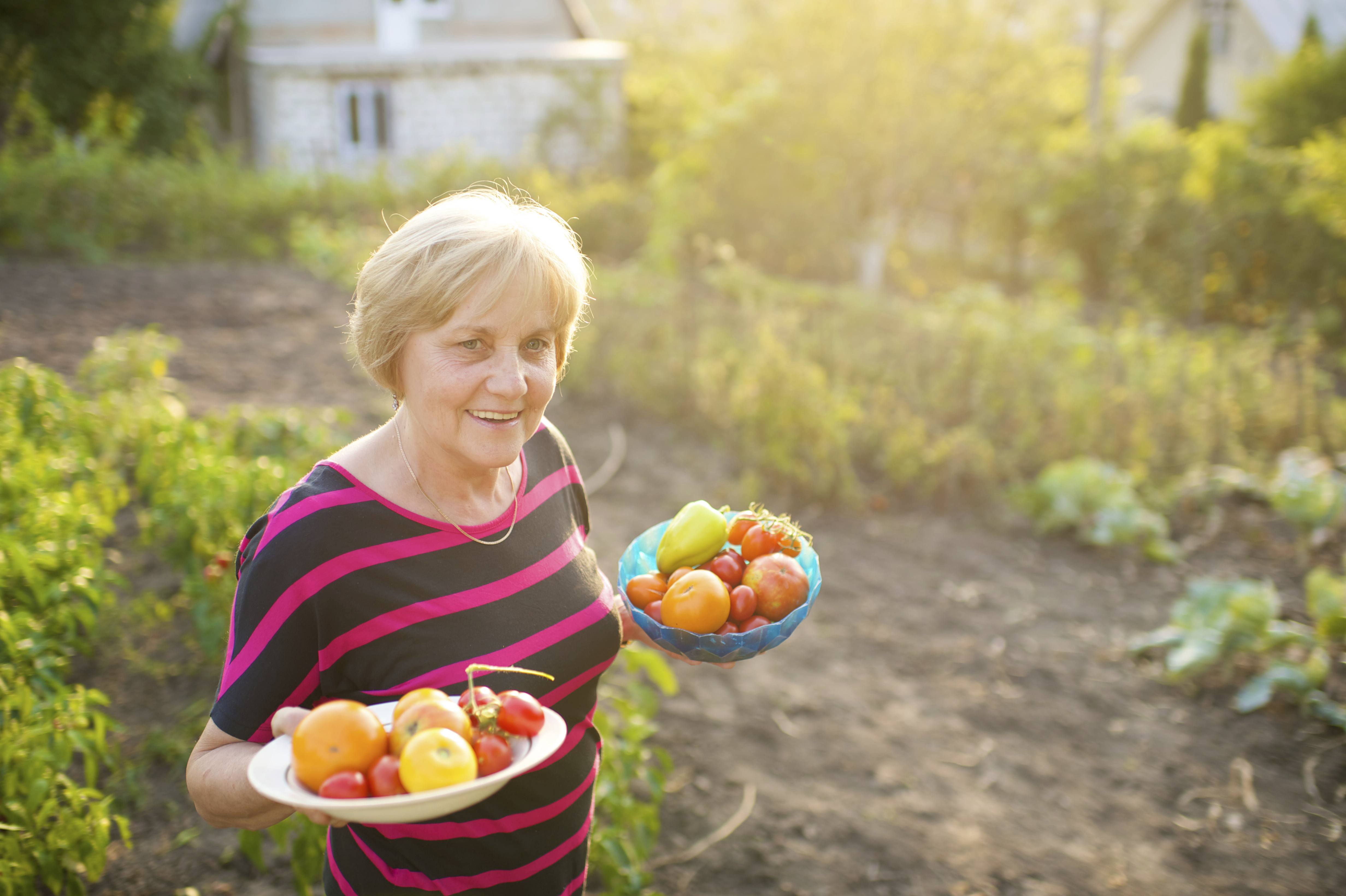 A woman in Romania holds two bowls full of fresh vegetables from the garden.