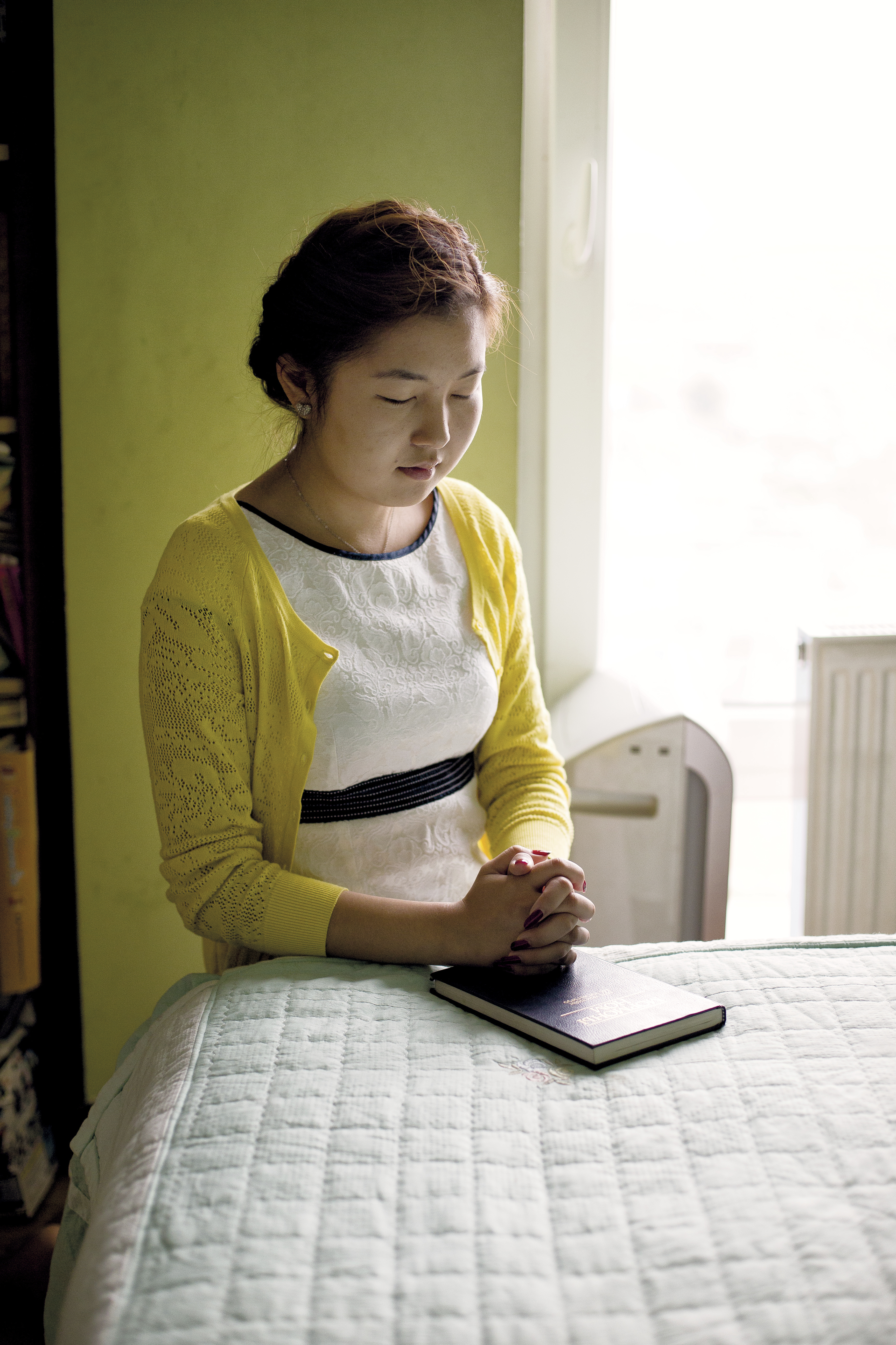 A young woman from Mongolia kneels by her bed and prays.
