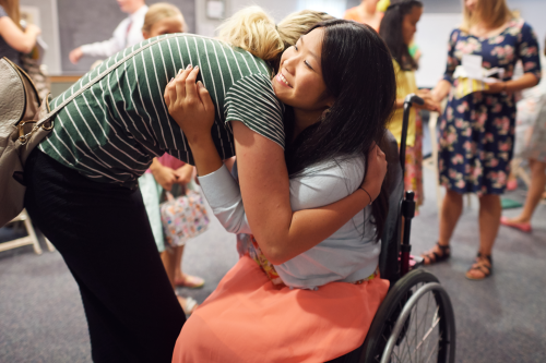 A girl in a wheelchair is talking with other young women and getting a hug