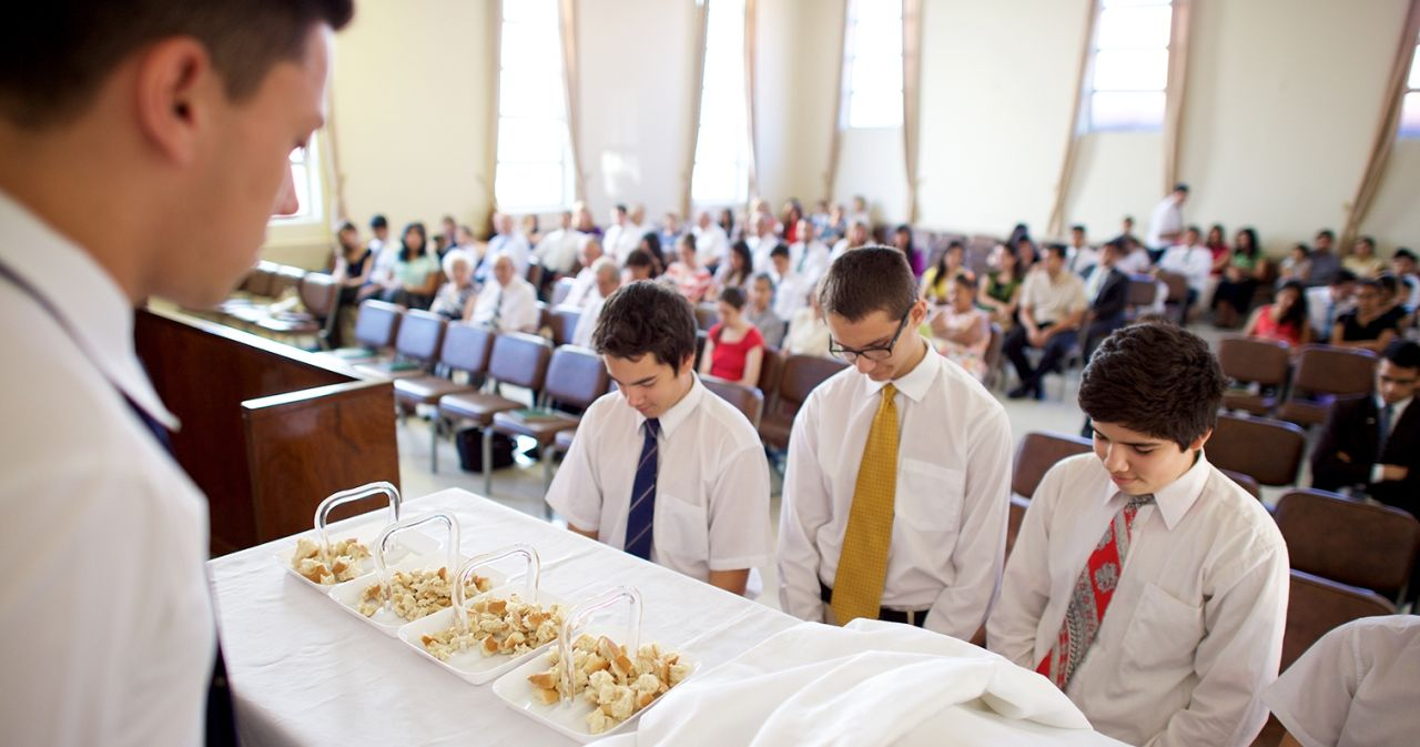 A group of young Aaronic priesthood holders bless and prepare to pass the sacrament to a congregation in a church