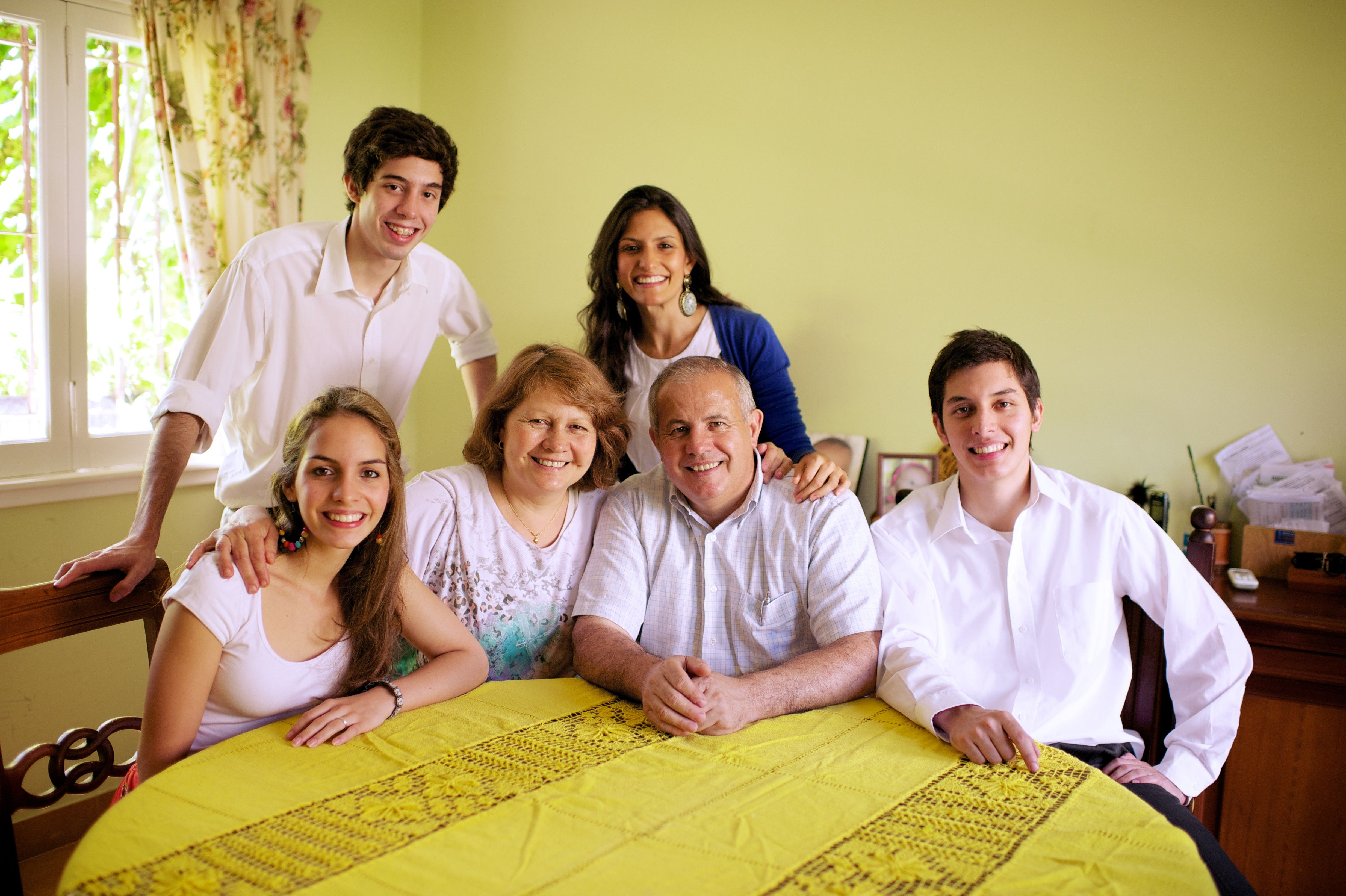 A family from Argentina sits in their home together around the dinner table.