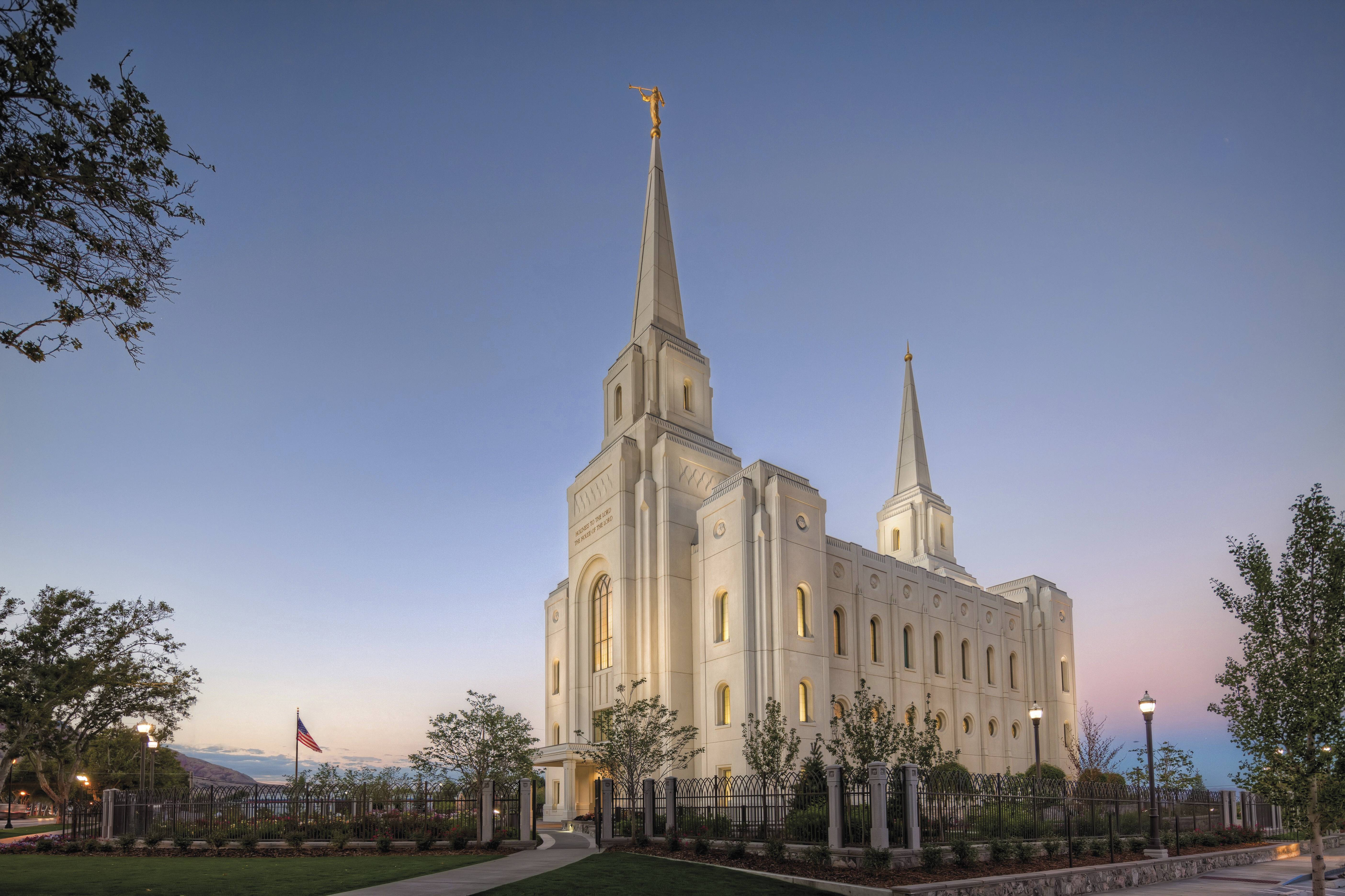 The Brigham City Utah Temple lit up in the evening, including scenery.