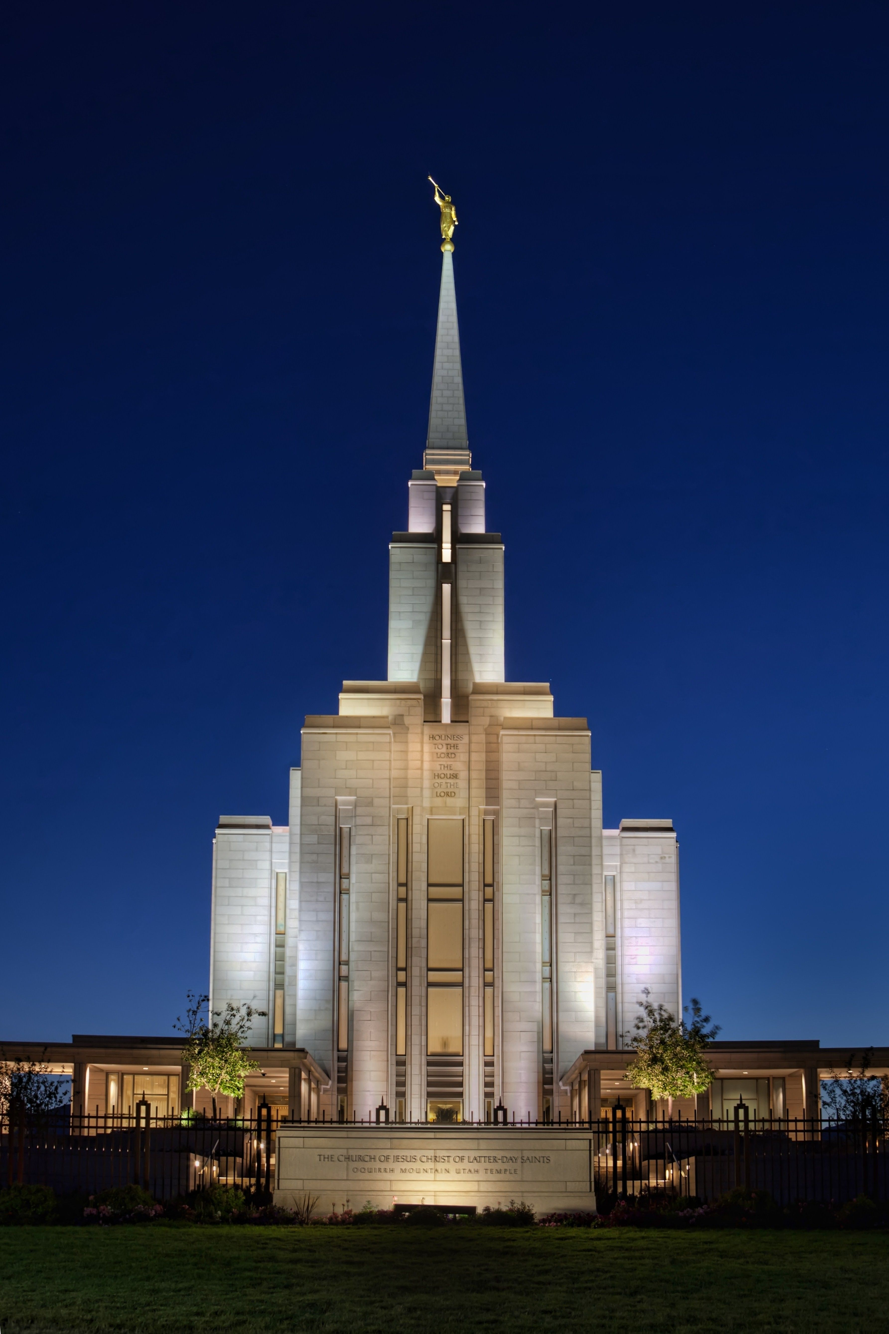 The Oquirrh Mountain Utah Temple in the evening, including the name sign and entrance.