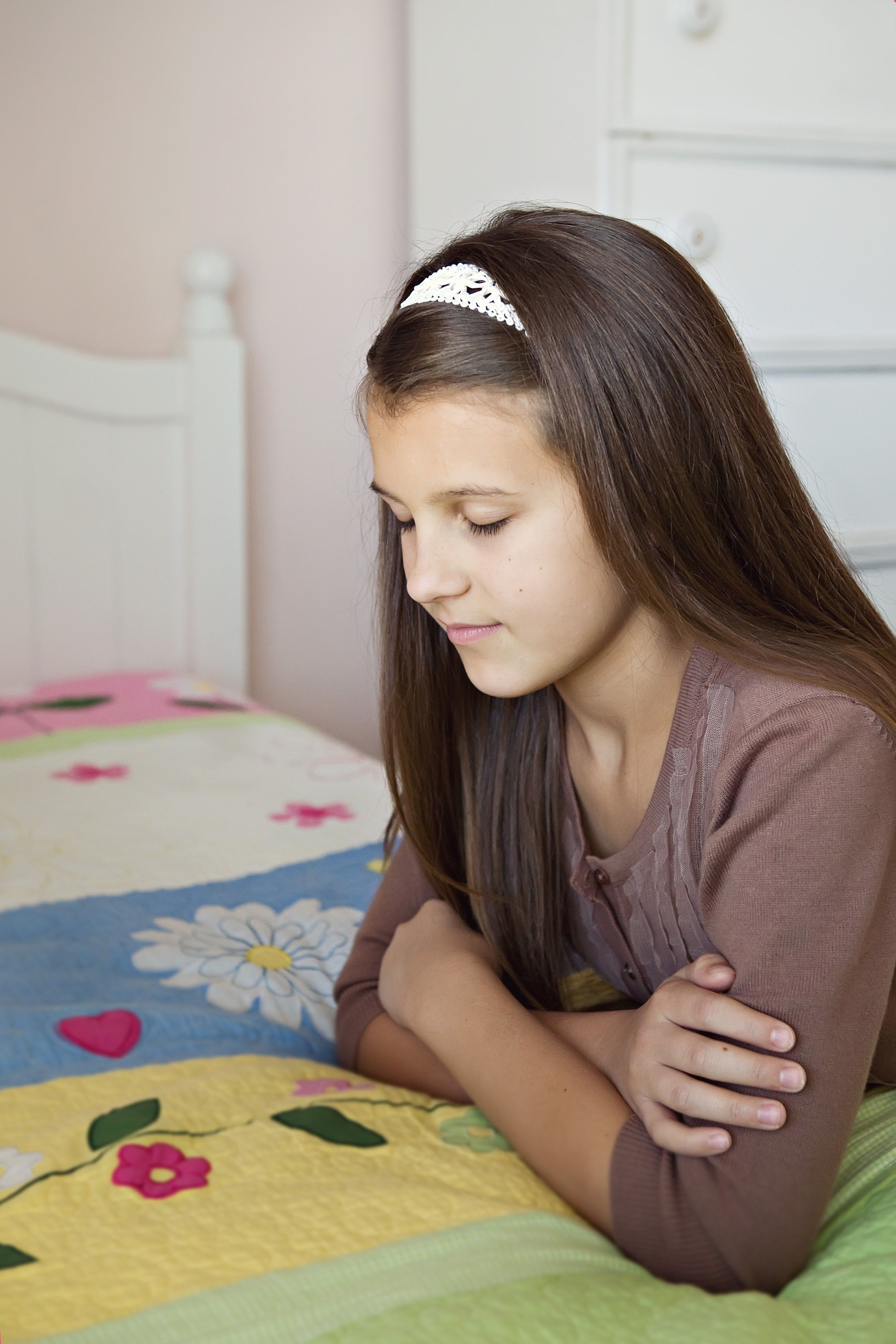 A young girl kneels in her bedroom and prays.
