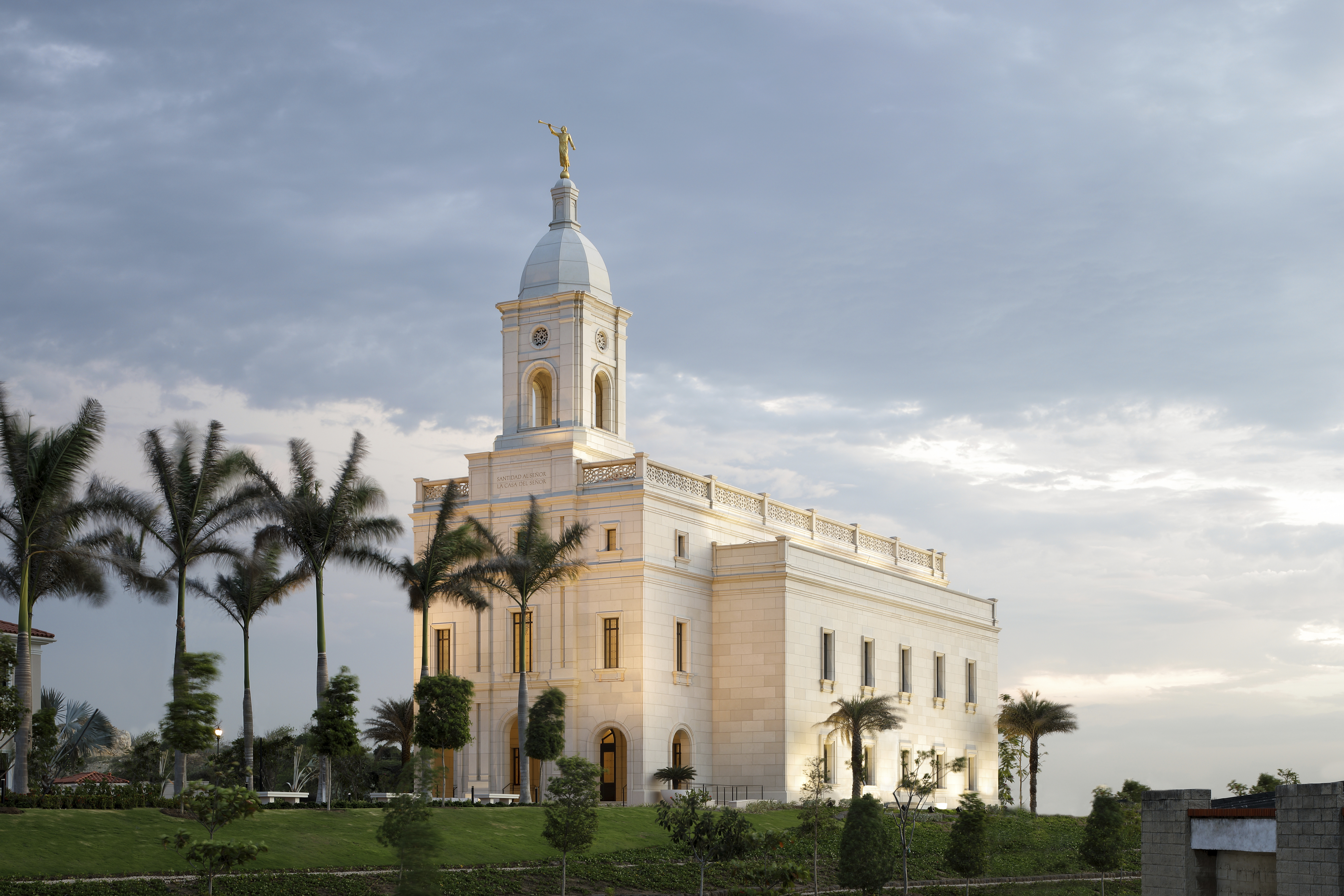 An evening picture of the Barranquilla Colombia Temple surrounded by palm trees.