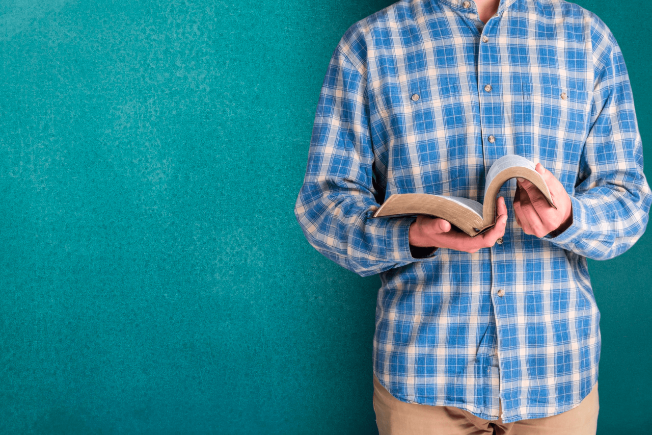 A man studies the Book of Mormon while leaning against a wall