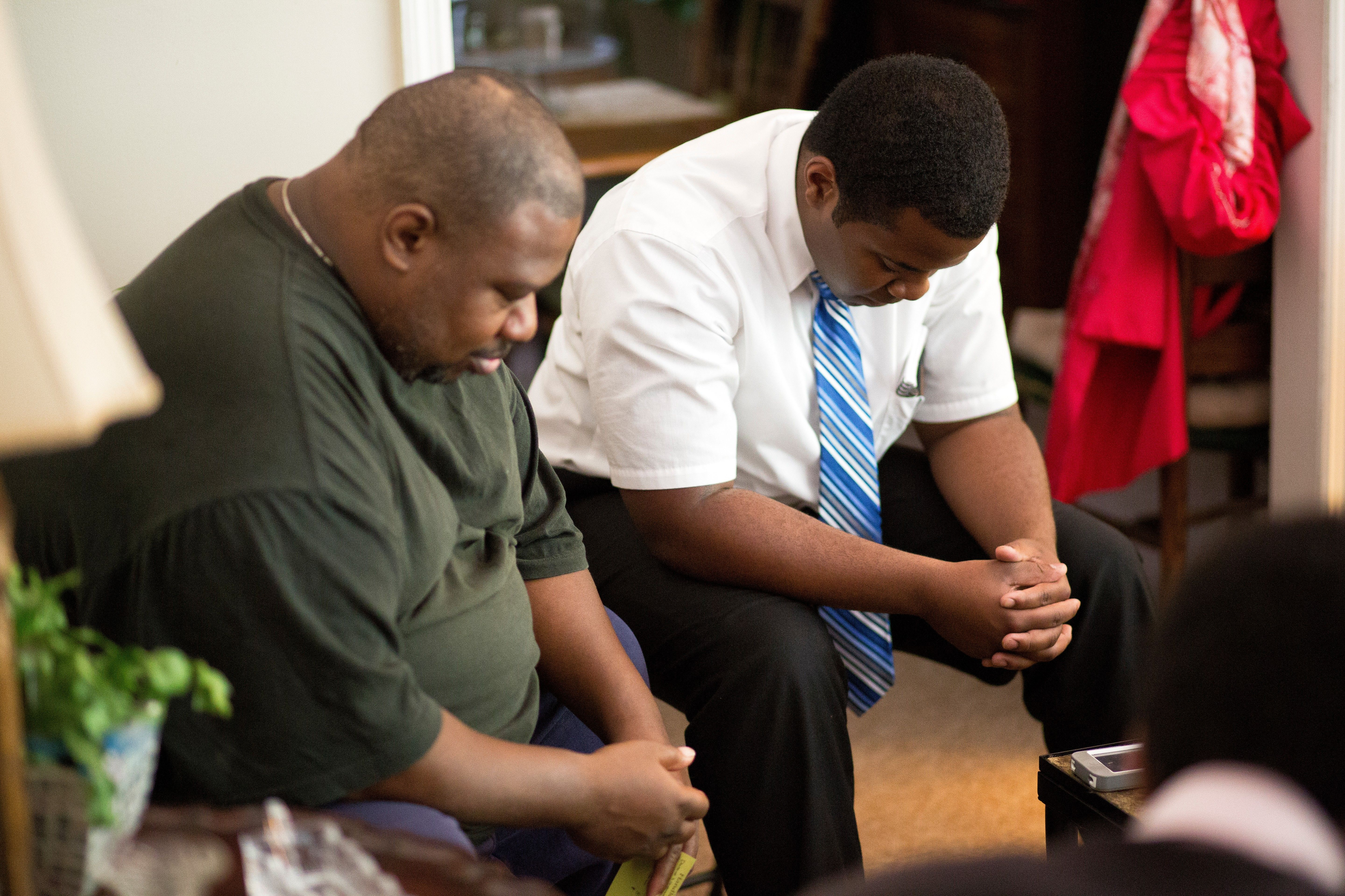 Missionaries sit and pray with a man they are teaching.