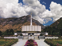 A wide-angle view of the Provo Utah Temple, with large mountains in the background and white clouds overhead.