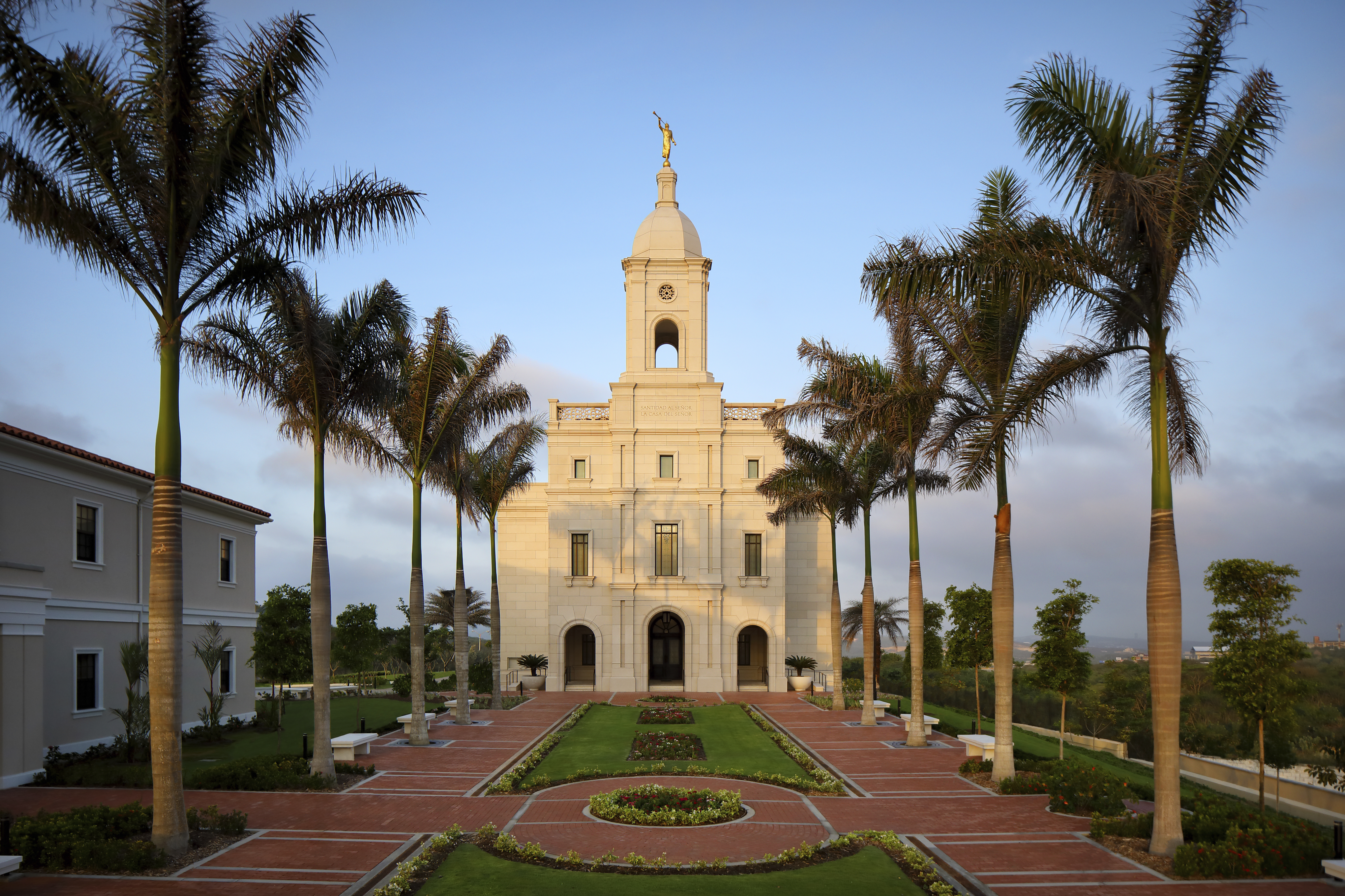 A front view of the Barranquilla Colombia Temple, with palm trees lining the walkway to the entrance.
