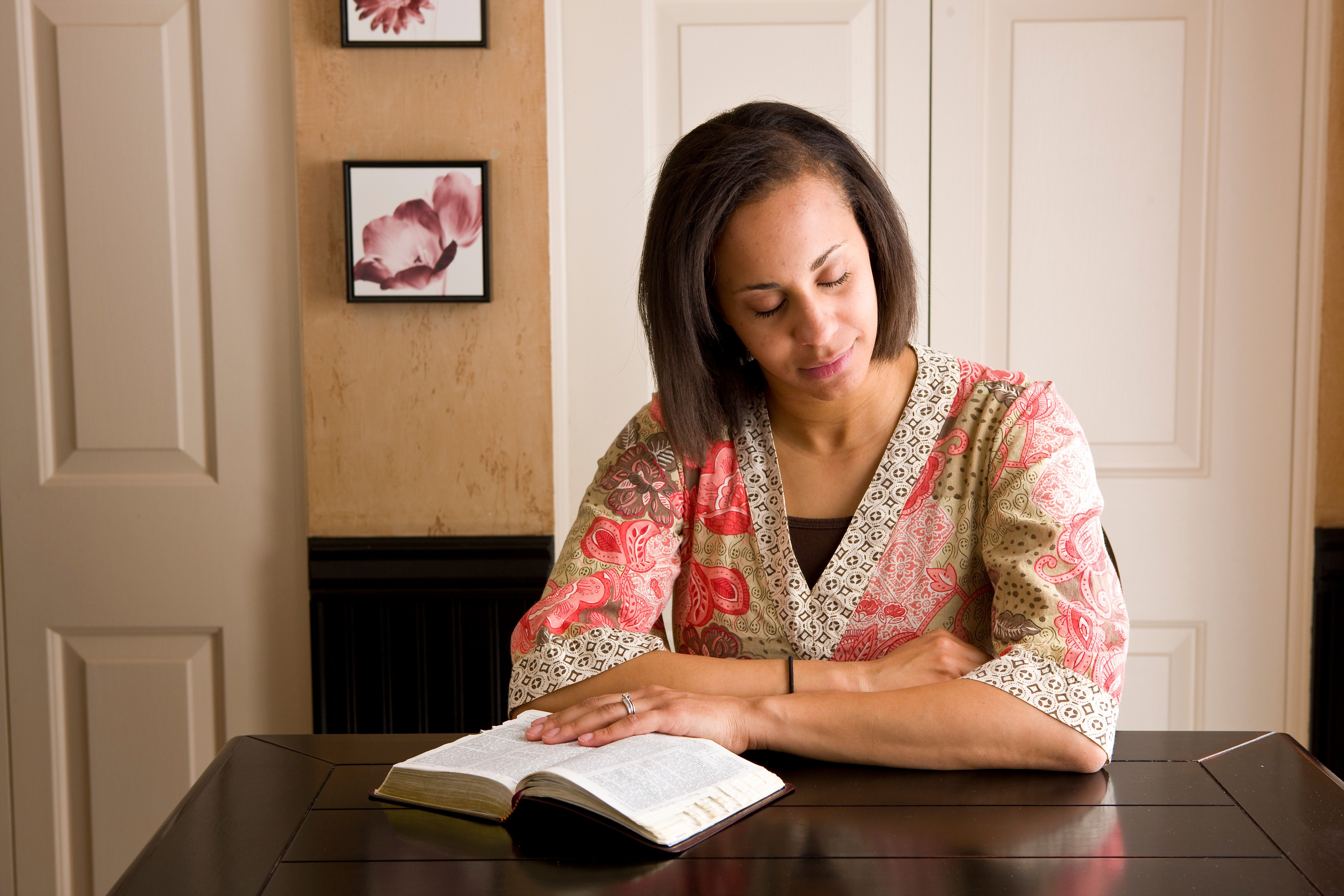 A woman studies her scriptures at the table and prays.