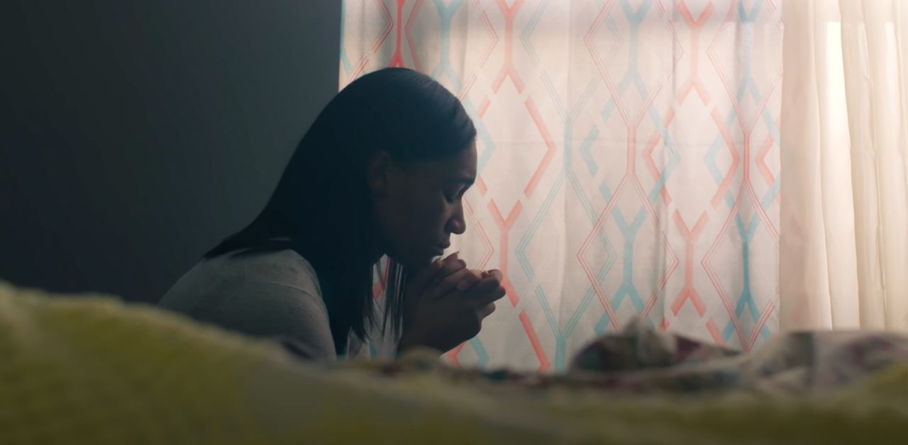 A woman prays for strength by her bedside