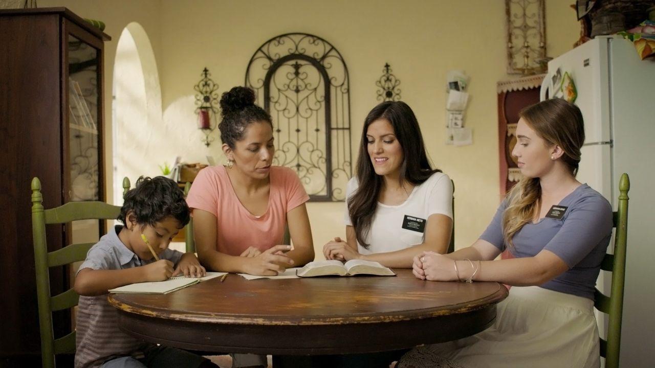 Dans la cuisine, deux sœurs missionnaires enseignent l'Évangile de Jésus-Christ à une femme et à son jeune fils