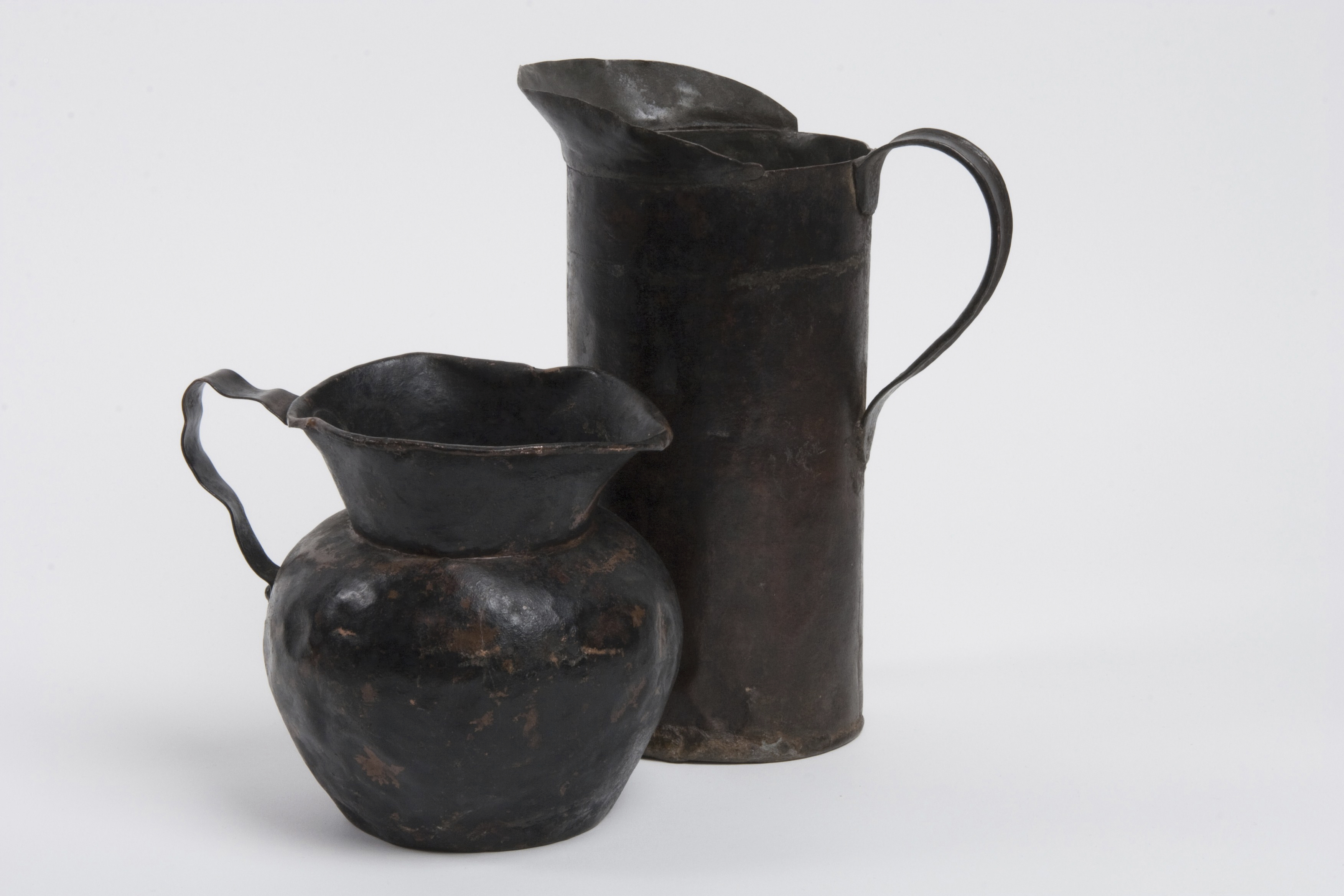 A photograph of two aged metal pitchers.
