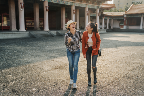 two young women walking and laughing