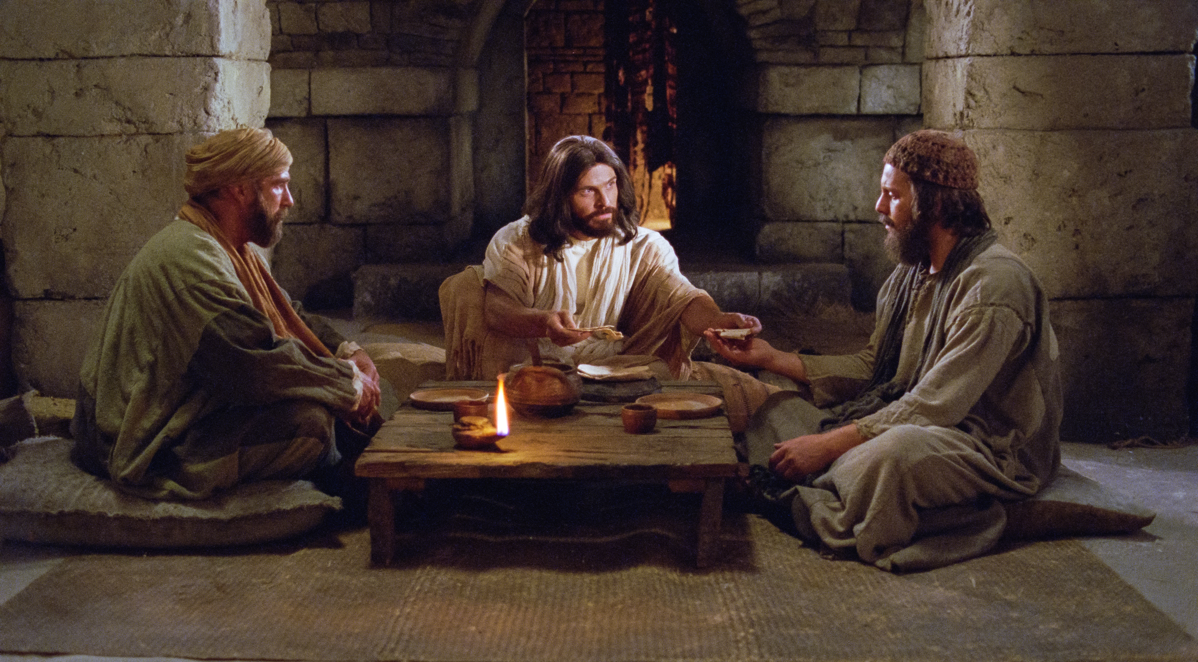 Christ communes with two disciples after having met them on the road to Emmaus.