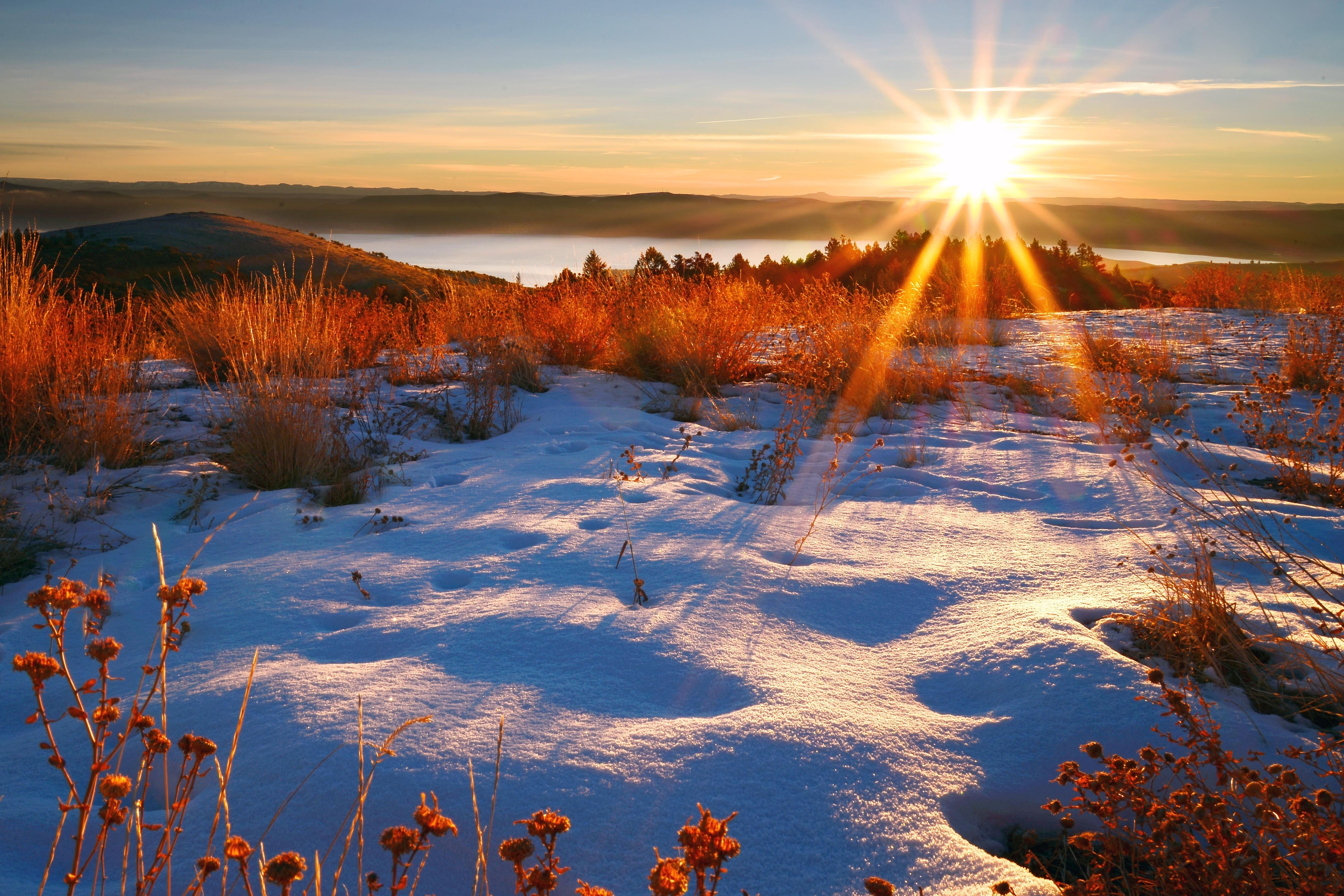 The sun rises over a lake surrounded by snow.