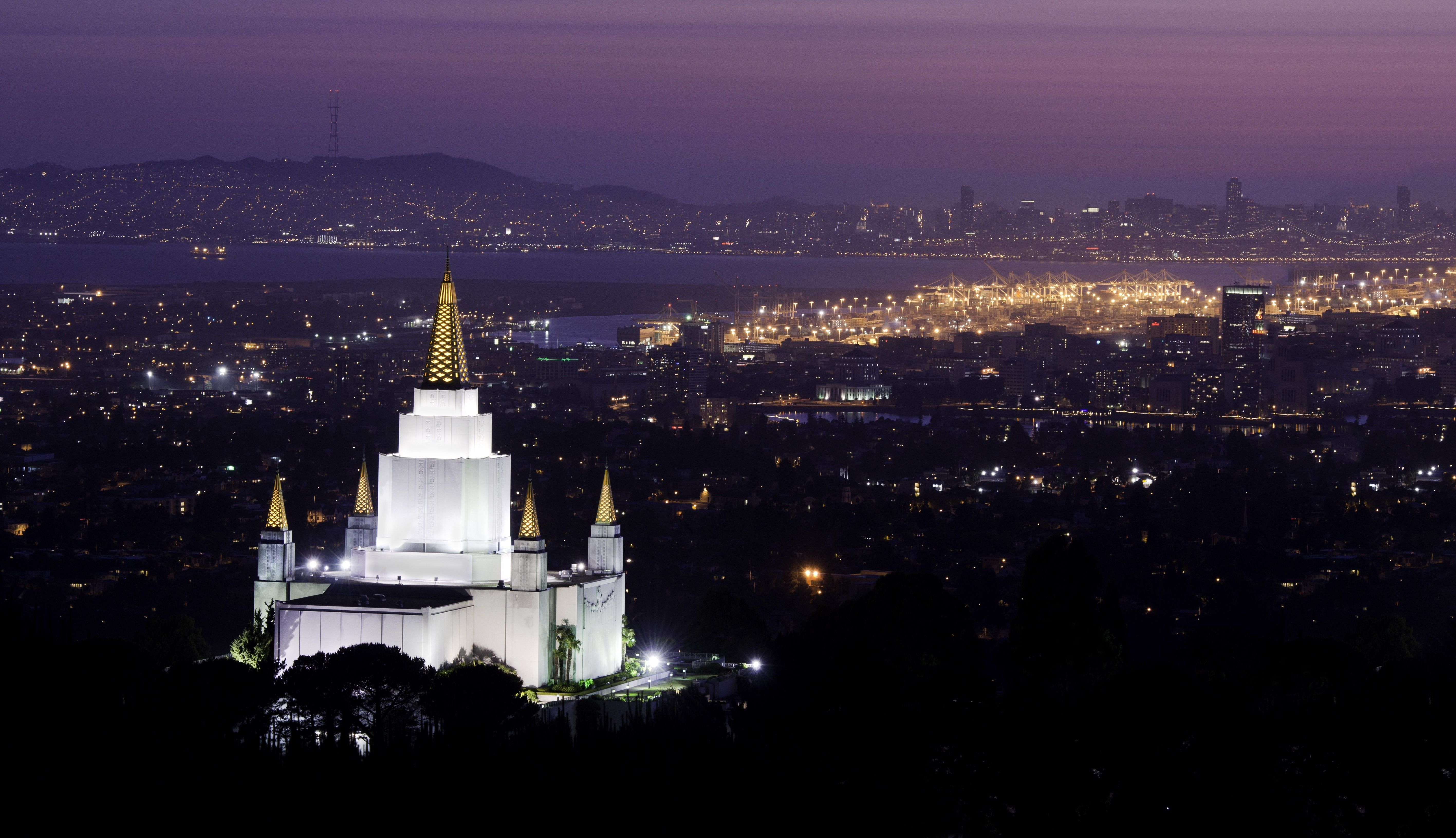 The Oakland California Temple in the evening, including the city.