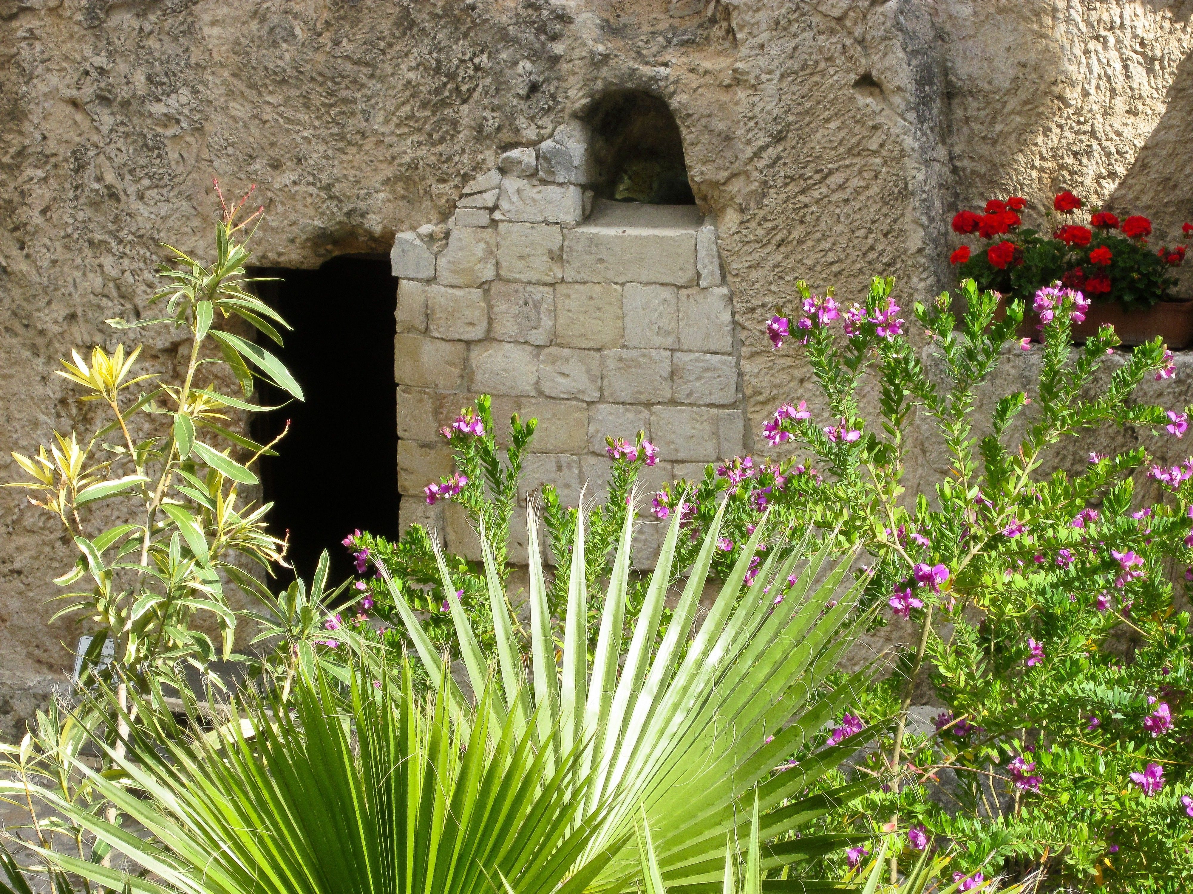 The entrance to the Garden Tomb amid native plants and flowers.
